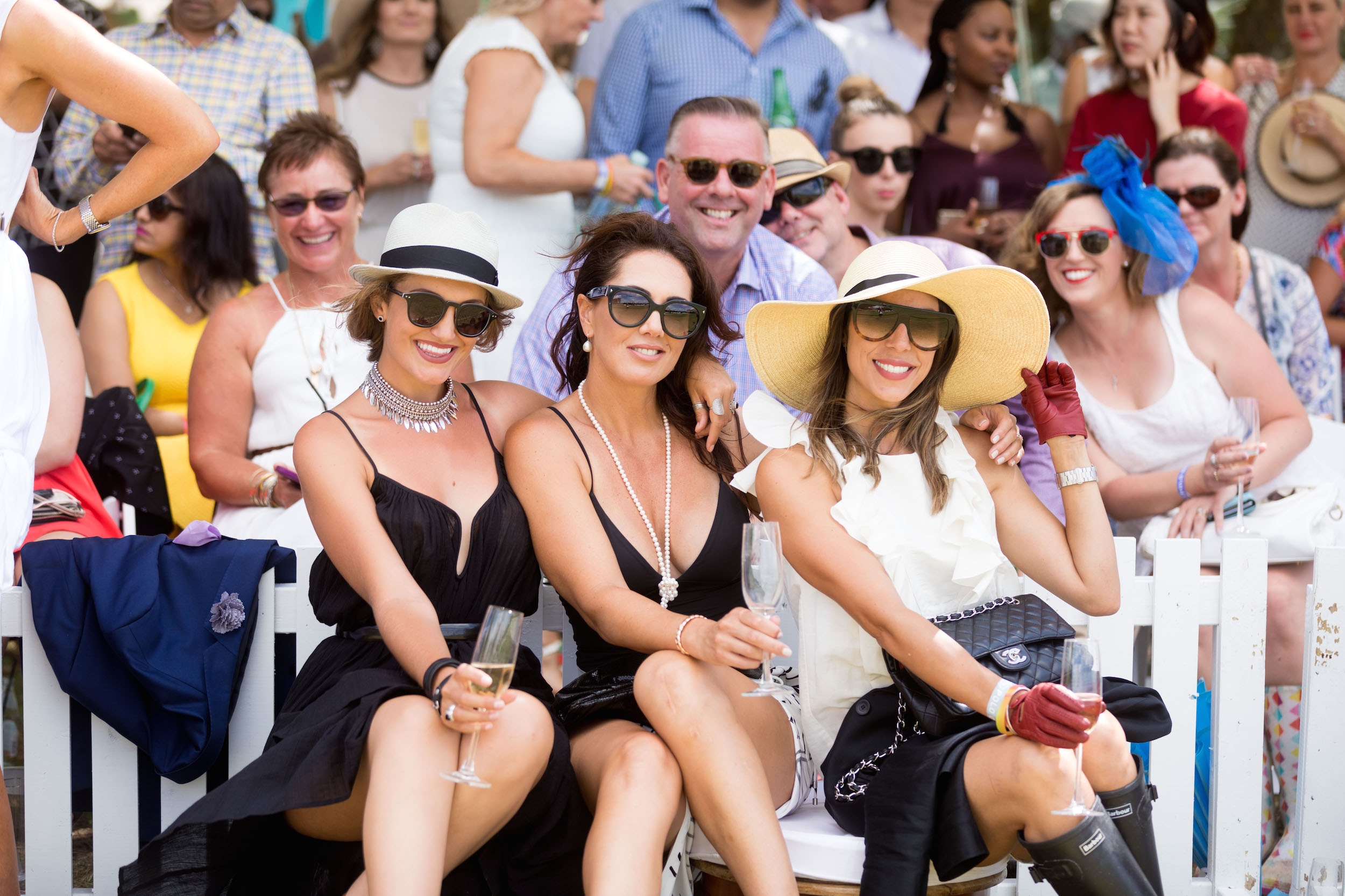 Three glamorous women in sunglasses sitting in front of a white fence and a crowd of people