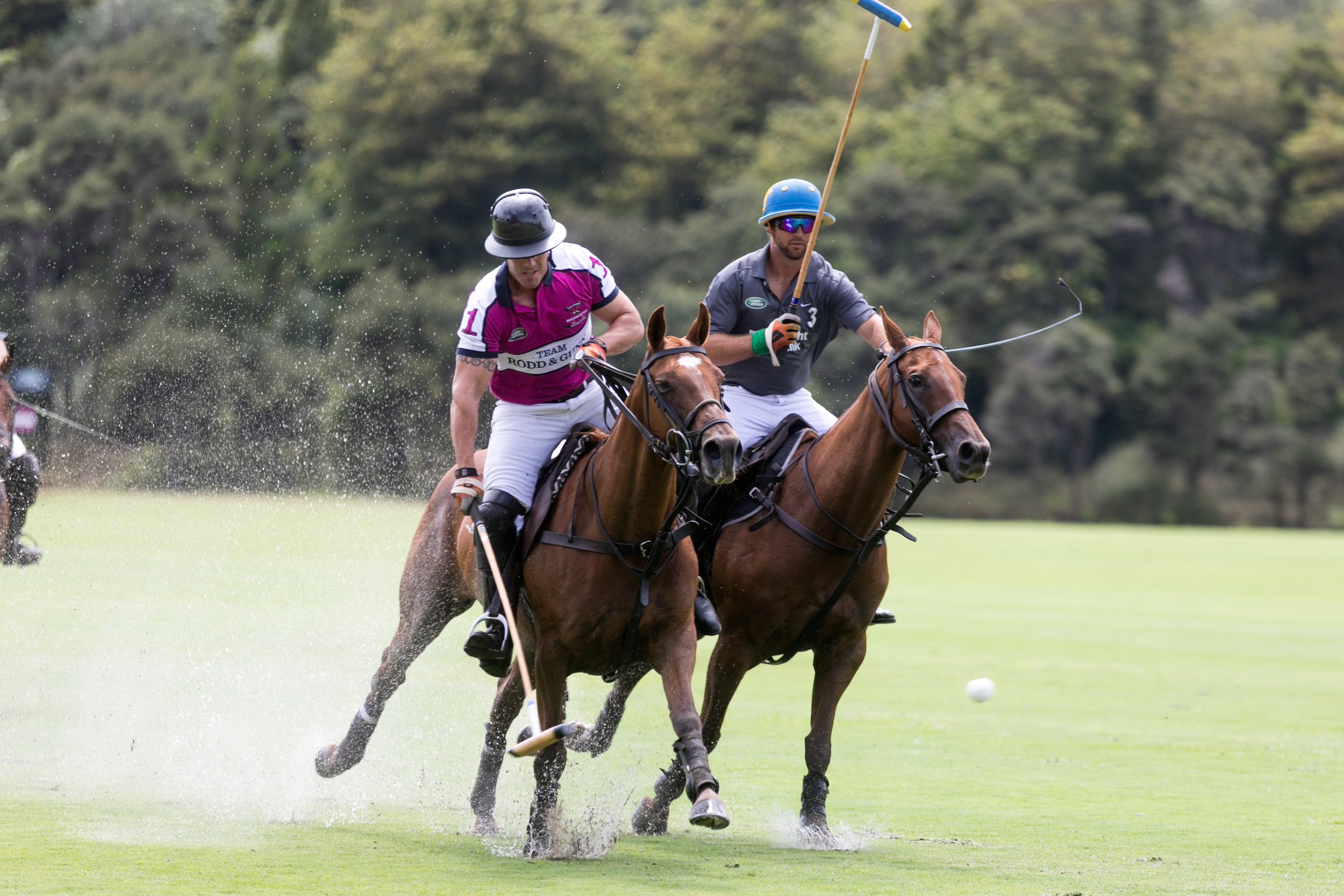 Two men on horses playing polo on a waterlogged pitch