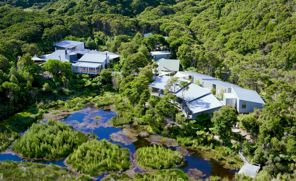 Aerial view of several buildings set into the green bush with pretty ponds by them