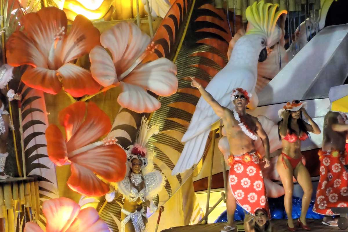 A Carribbean island-style float with men in sarongs and women in bikinis dancing amongst giant palm leaves and Hibiscus flowers in Rio