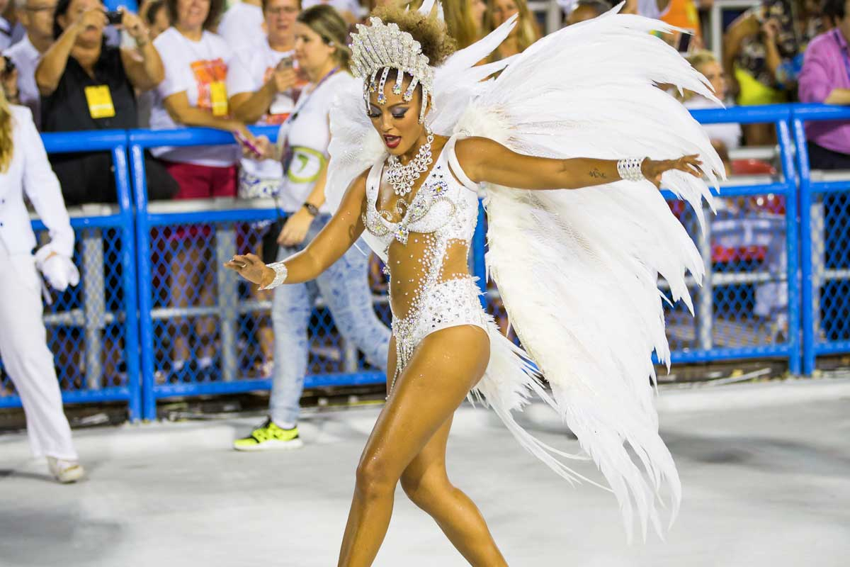 Woman in white feathered wings dancing in the street with the crowd watching on at the Rio carnival