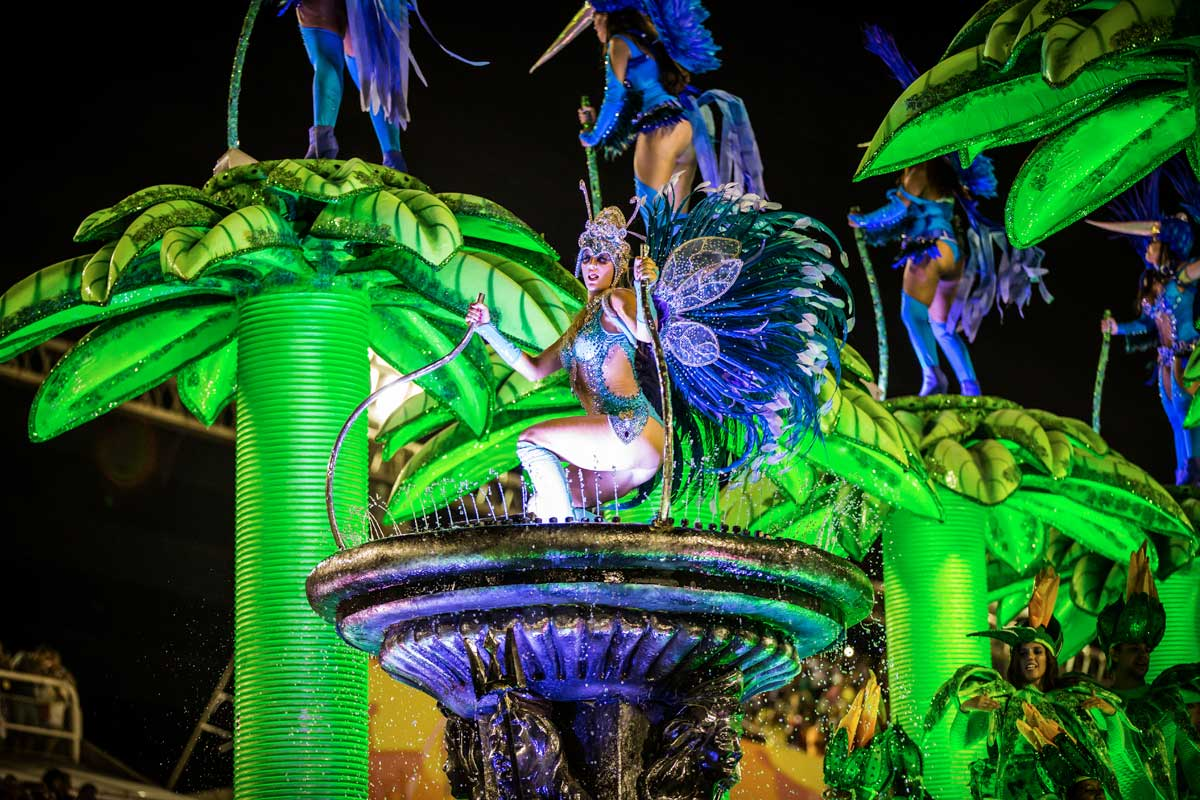 A lighted up green and blue float with women dancing atop it