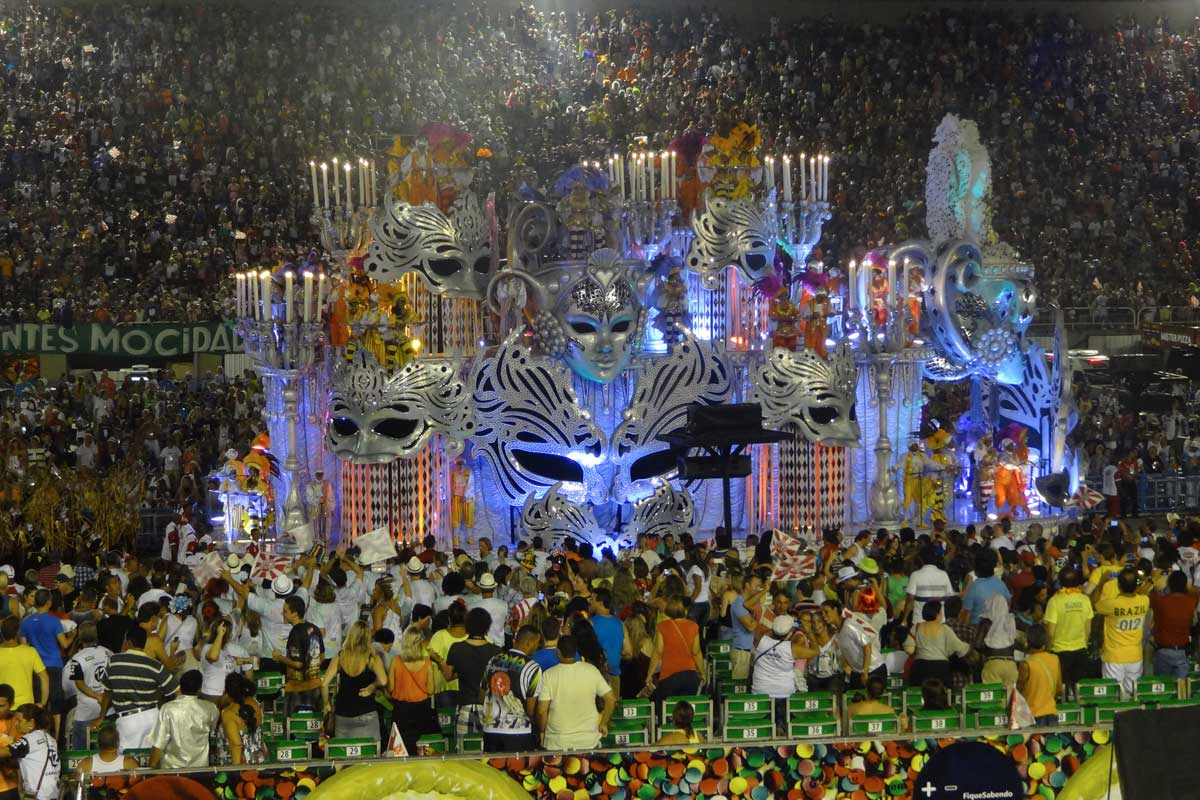 A float of giant masquerade masks going through the crowd at Rio