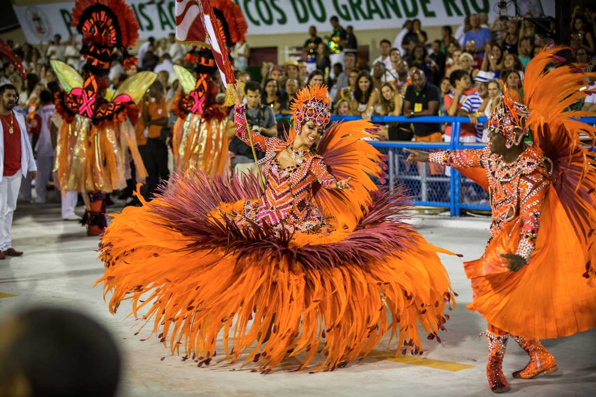 Woman in an orange feathered dress and headdress holding a flag and dancing with the crowd watching from behind fences at the Rio carnival
