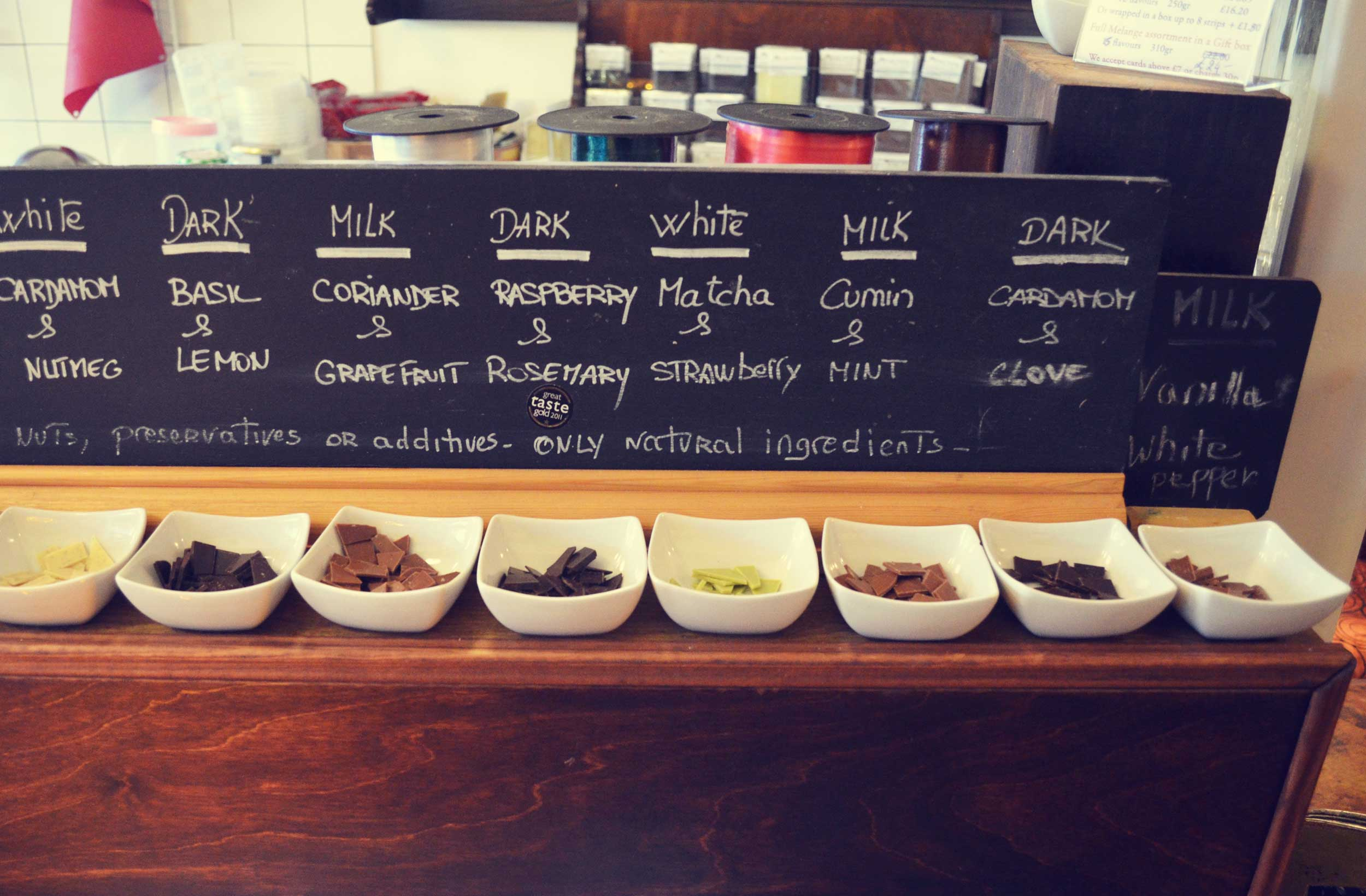 Bowls containing variously flavoredchocolate pieces all lined up in front of a blackboard, Peckham, London