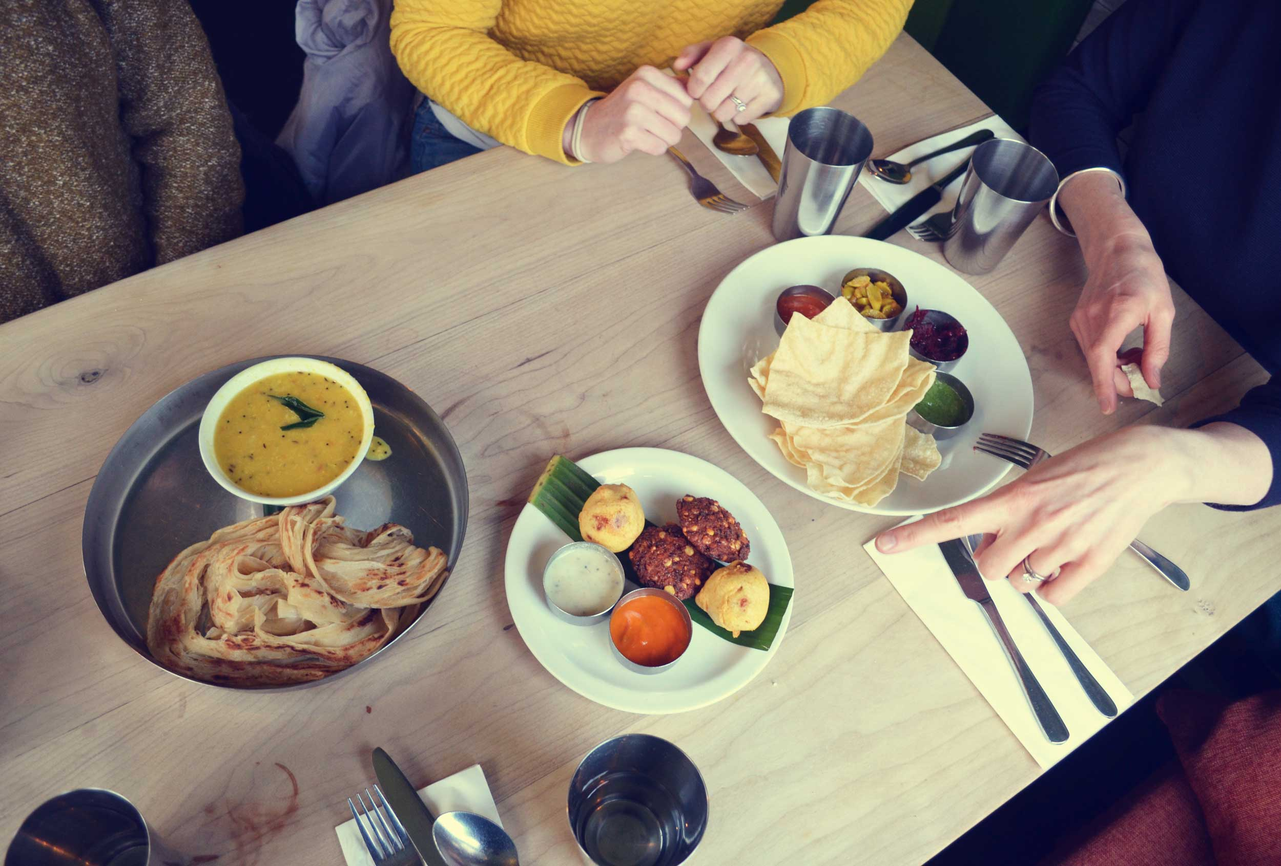 Indian food spread in three plates on a wooden table at Ganapati's, London