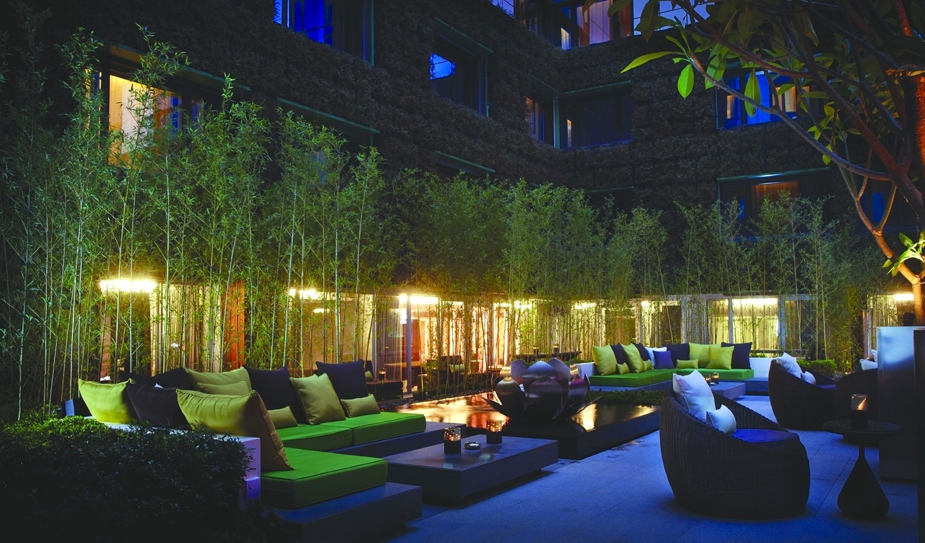 Comfortable outdoor sofas with green cushions interspersed with trees and surrounded by buildings at The Mira