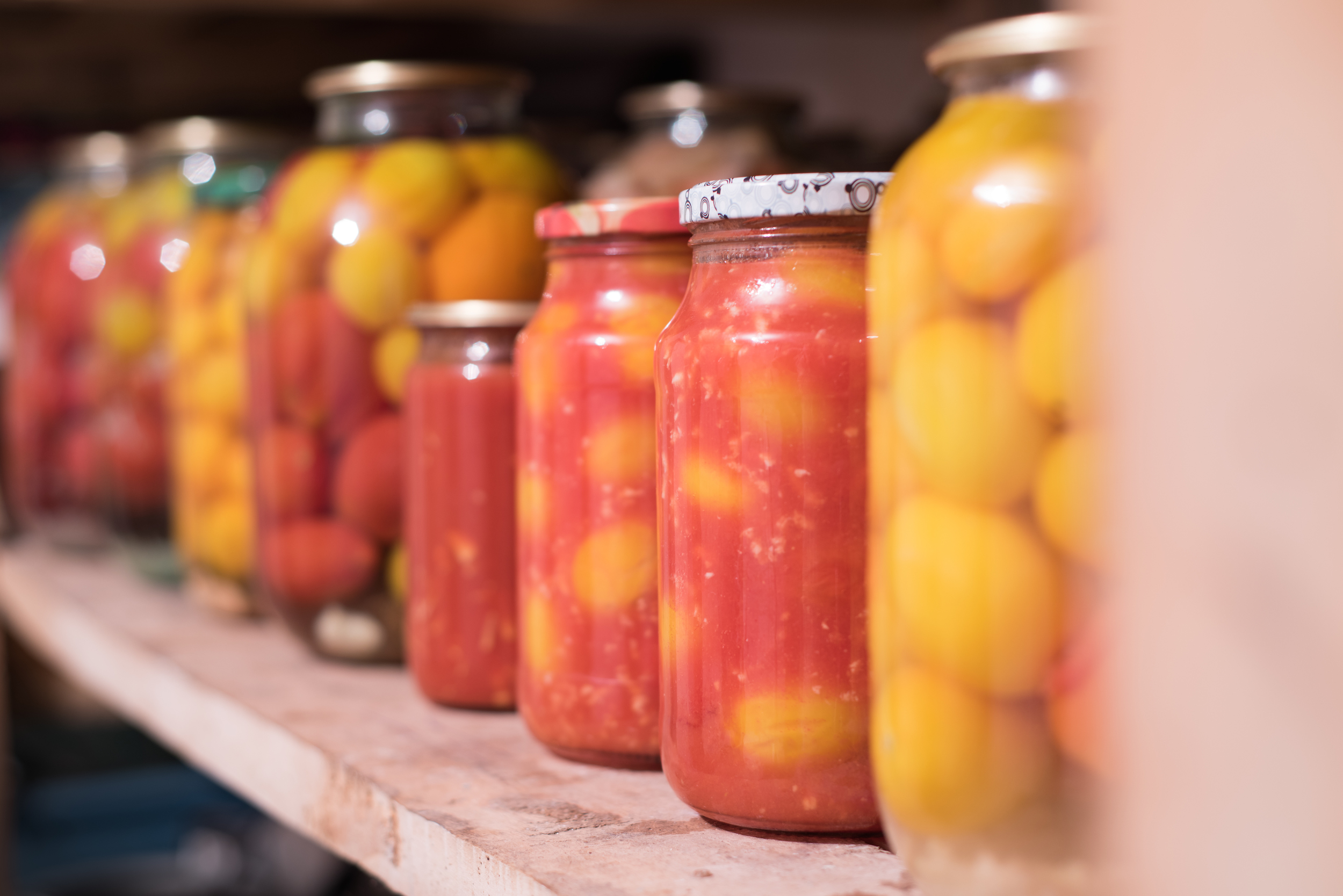 Shelf showing pickled tomatoes in glass jars