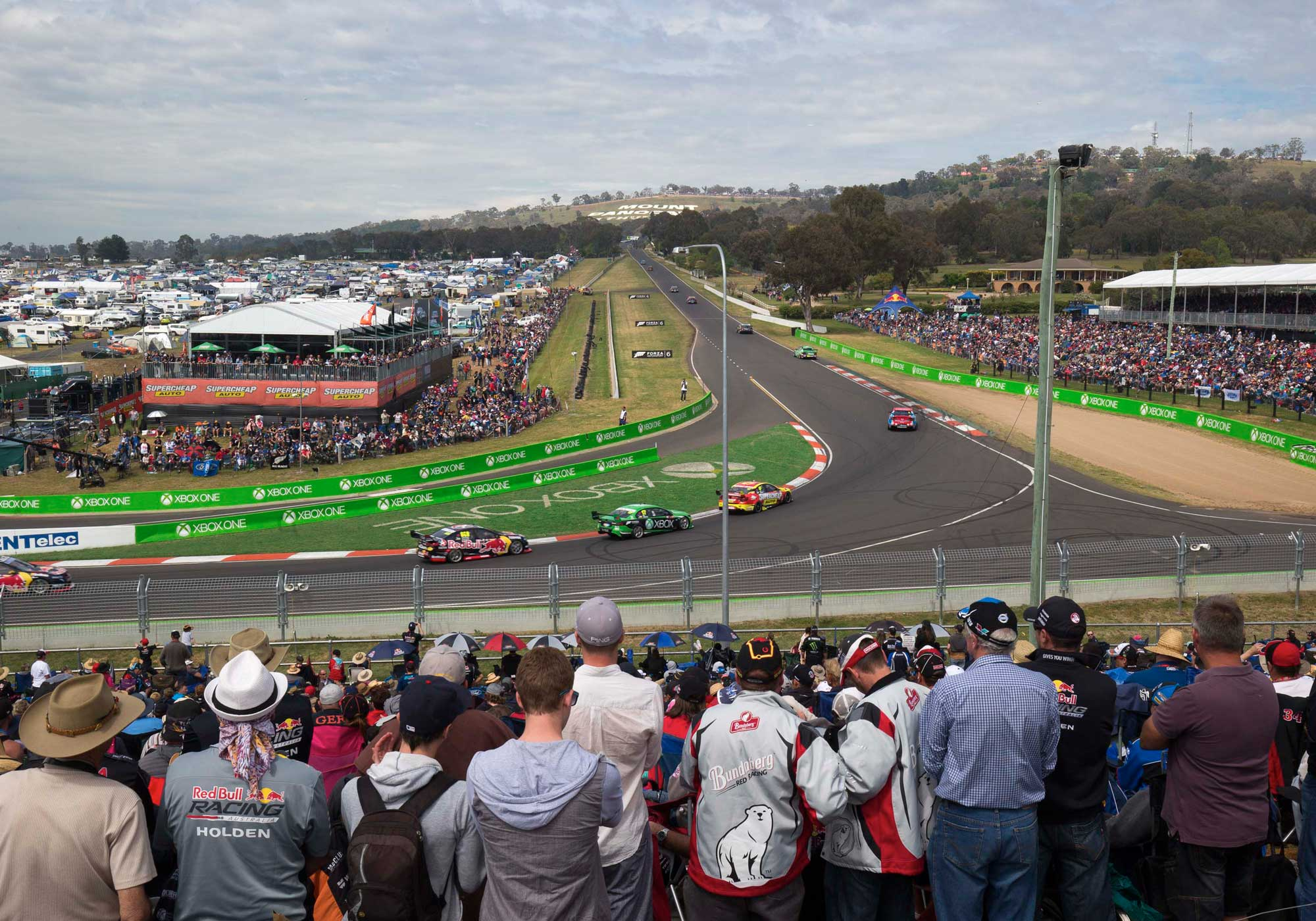 Crowds on either side facing down a bend and a straight stretch of the track at Bathurst 1000