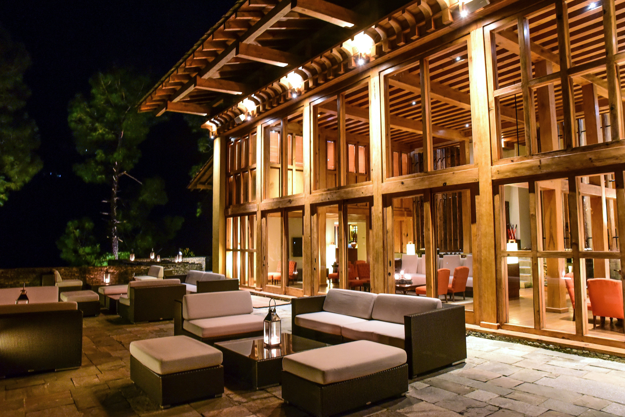 Looking at an open, airy and wooden building with restaurant seating inside and outdoor seating arrangements on the tiled floor outside it at night in Bhutan