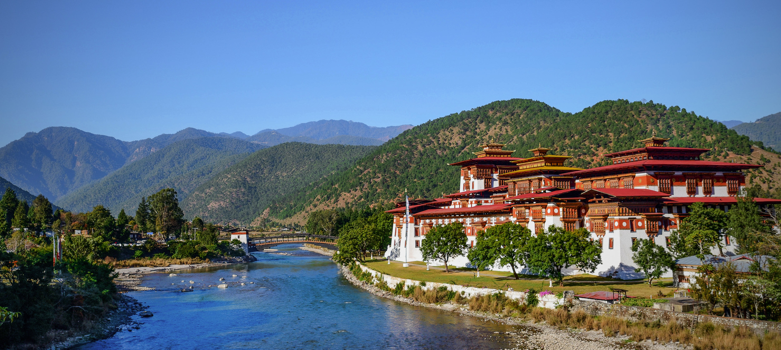Ancient white and red fortress on the right side of a riverbank, with mountain in the background.