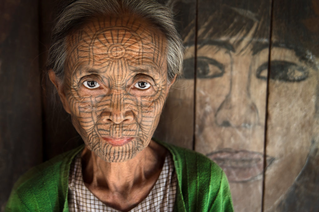 One of the elder generation of women in a Chin village near Mrauk U with a tattooed face. The ancient custom was thought to prevent invaders from stealing away the local women; the practice continued as a cultural tradition and was regarded as a sign of beauty.