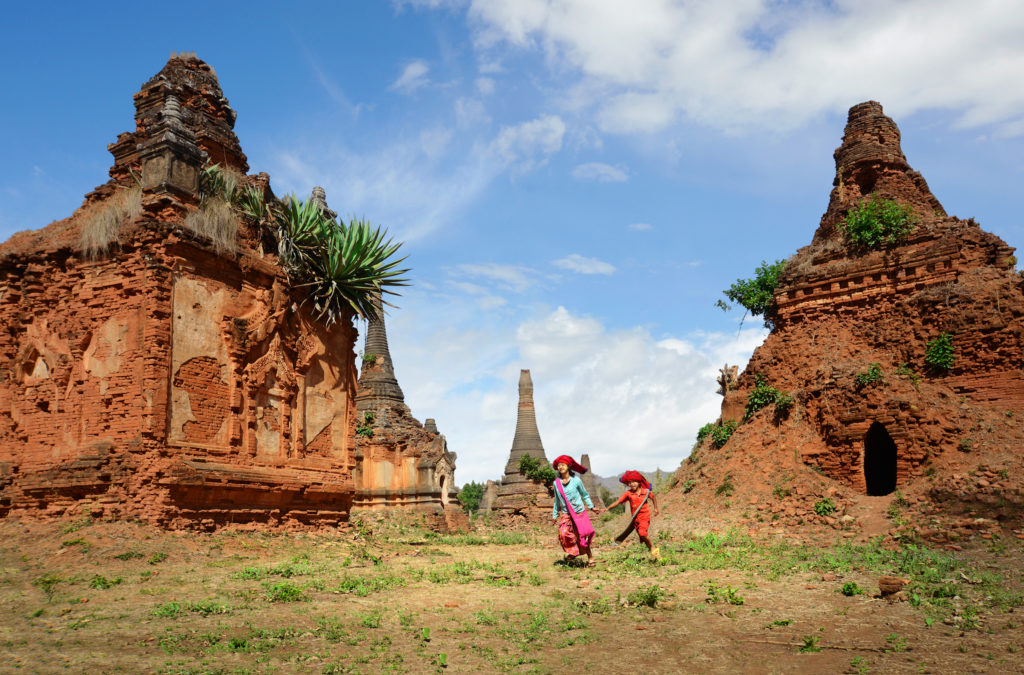 Two children from the Pao-O tribe run through an area of ancient red brick Buddhist stupas near the village of Indein.