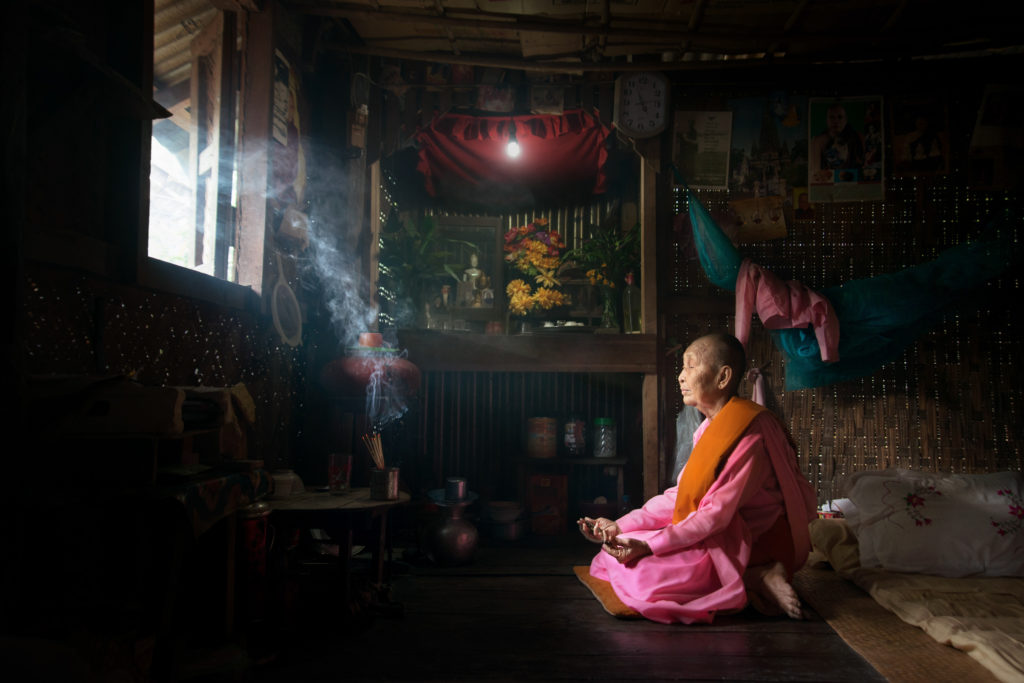 An elderly nun praying in her room at the nunnery. Nuns shave their heads and typically wear pink robes with an orange sash, although a small number wear brown robes. Nuns are not encountered as frequently as monks.