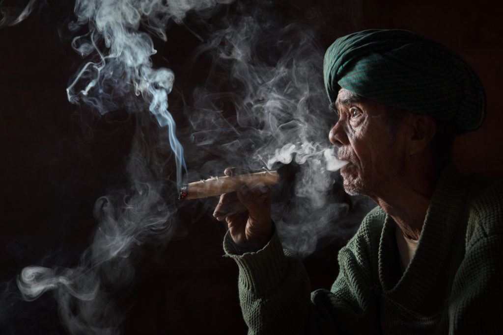 A low-light portrait of an elderly man smoking a open-ended cheroot cigar.