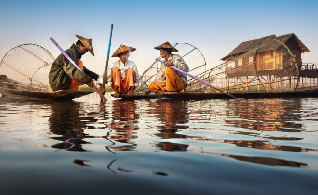 Three fishermen huddle together at dawn.