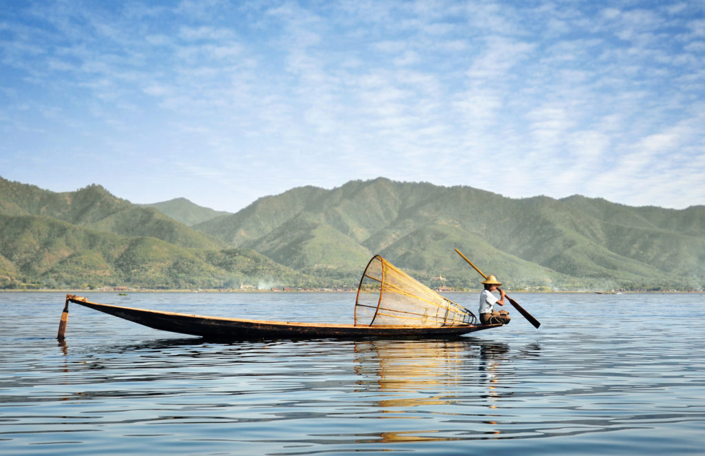 A fisherman on Inle Lake paddling a long distance in his wooden boat, which is equipped with a conical fishing net.
