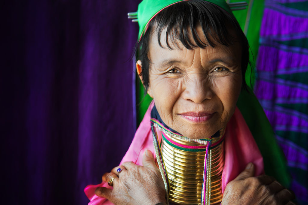 Portrait of a Kayan (sometimes referred to as 'Padaung') woman who works on Inle Lake creating and weaving colourful fabrics. The brass neck rings are quite heavy, and are worn to give the appearance of an elongated neck, which is thought to be beautiful. They are removed for bathing and sleeping, and the neck remains strong and healthy without the rings.