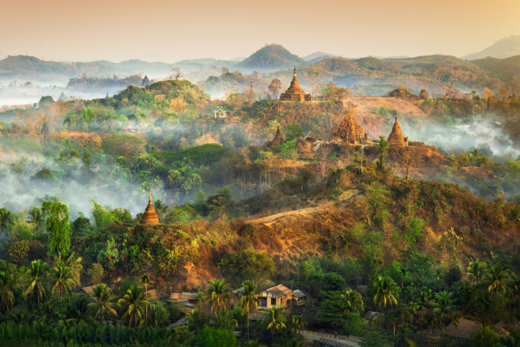 Sunrise over Mrauk U, where more than 700 temples and stupas of unique Arakan design dot the hilly landscape. Smoke hangs in the air as people living here make fires to boil water and begin cooking.