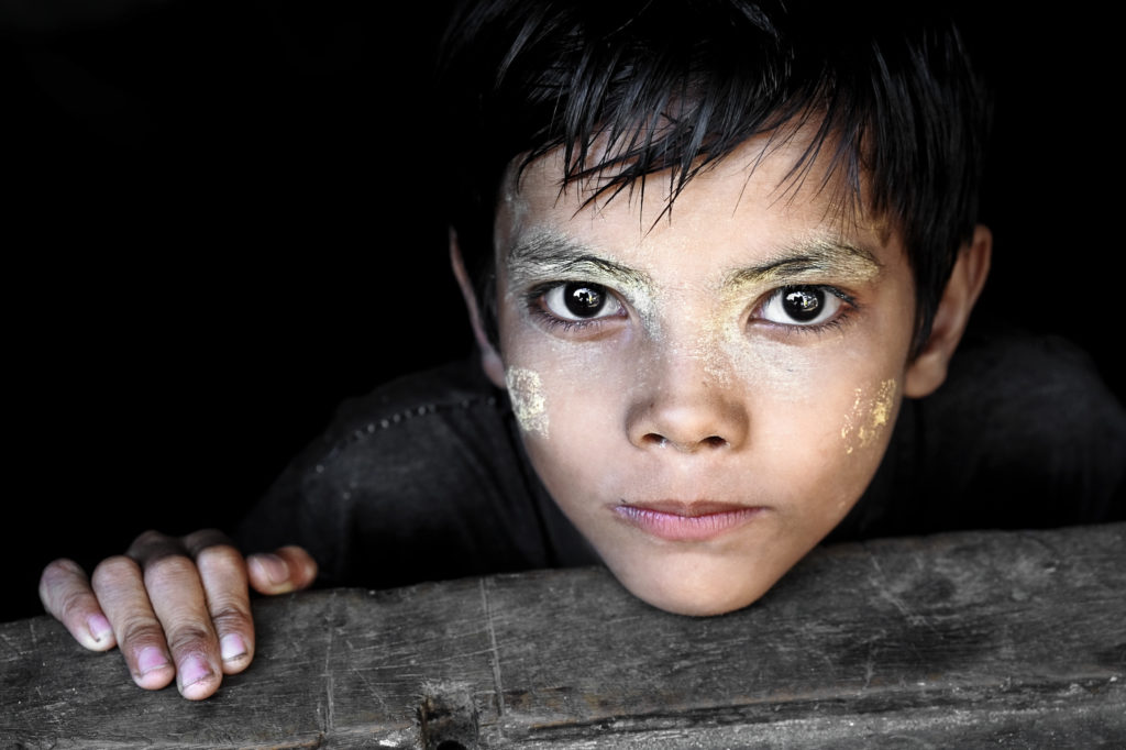 A boy —the son of Mu Mu —wears thanaka paste on his skin that has been applied in circular patterns, as a way to express his individuality.