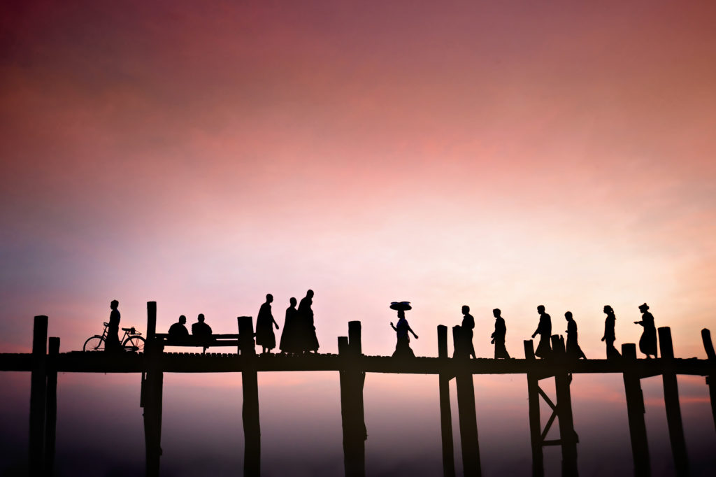 Silhouettes of local people crossing U Bein bridge at sunset.