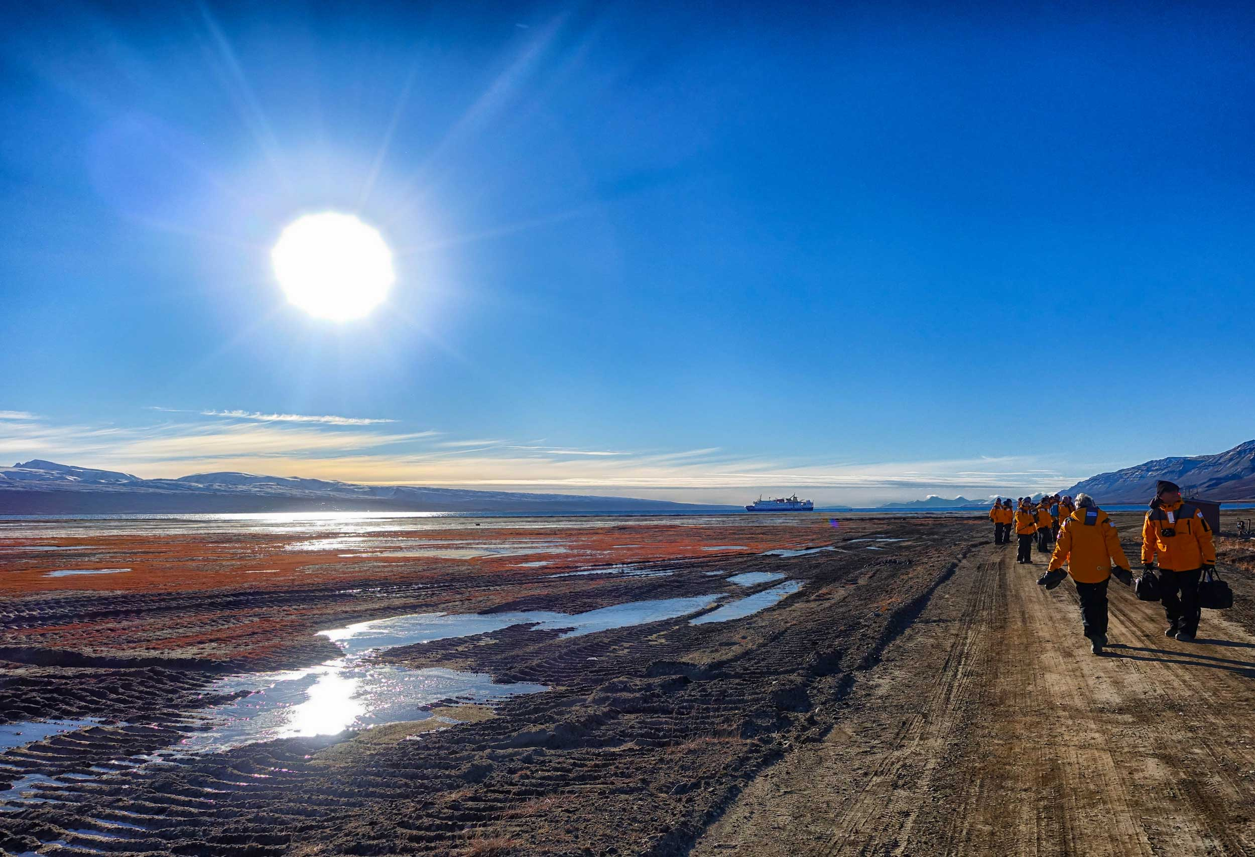 Group walking across flat, barren terrain, a very bright sun and a ship on the sea in the distance, Greenland