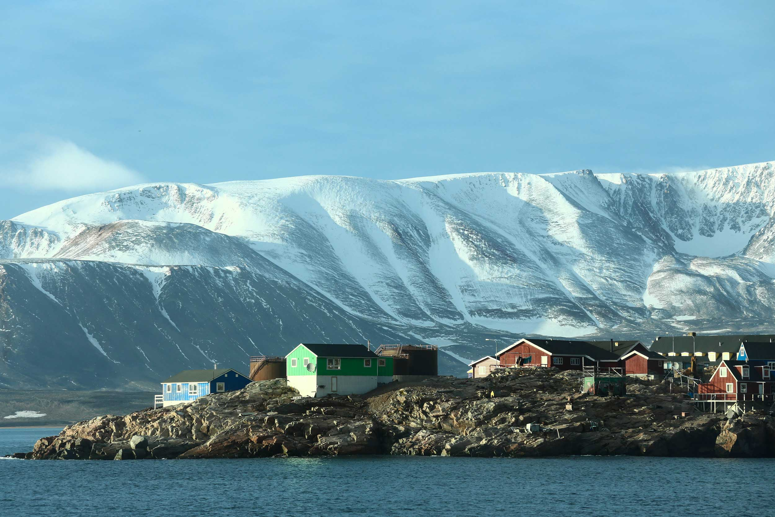 Buildings on a rocky outcrop by the sea with ice covered mountains in the background, Greenland