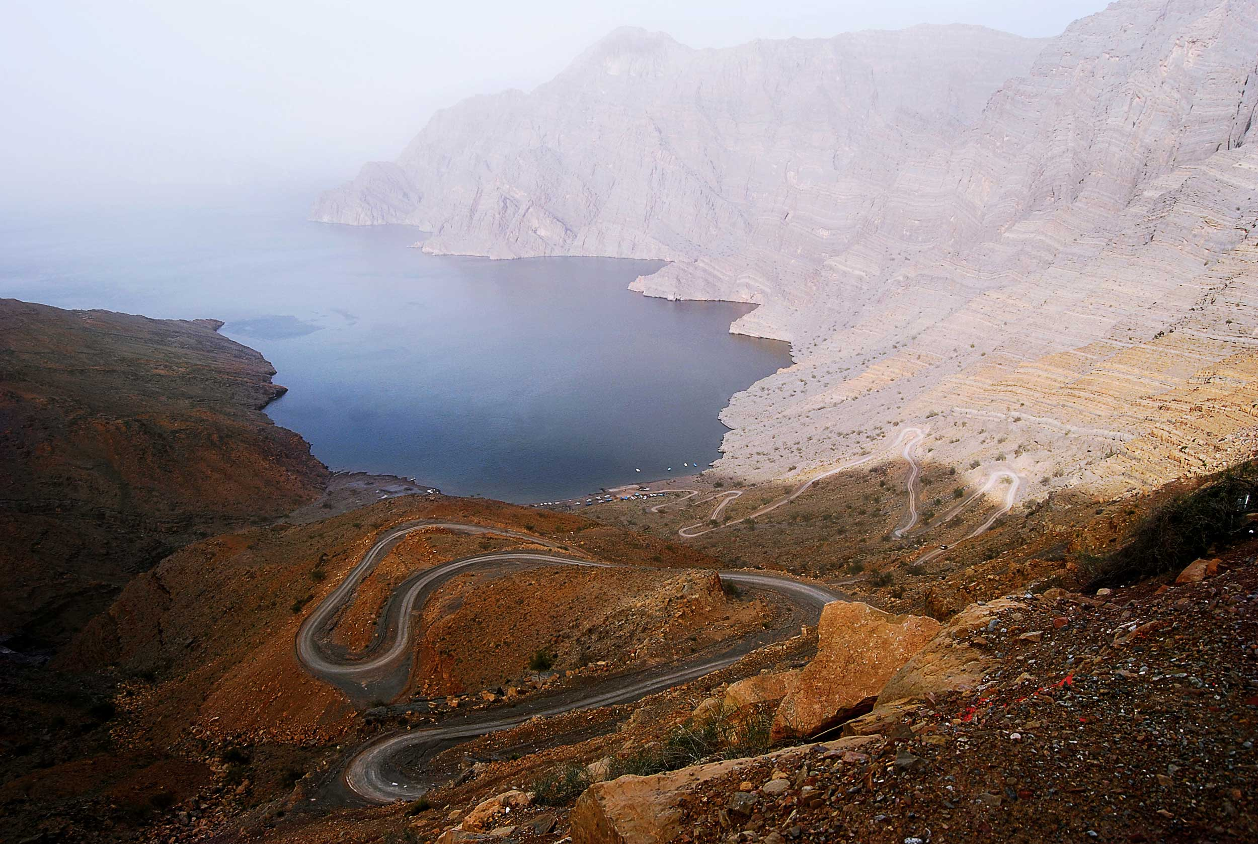 An extremely long and winding road going down a brown mountainside to the sea with white cliffs and hills in the distance, Musandam Peninsula, Oman