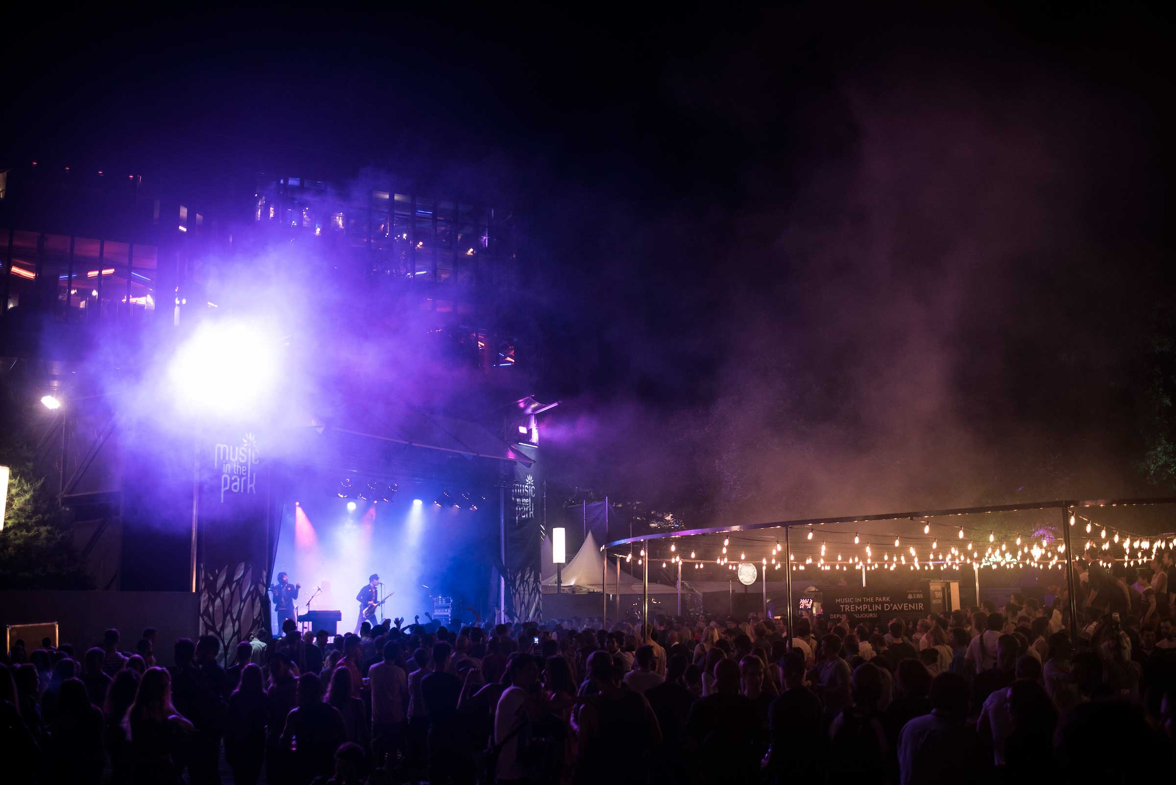 a duo performing onstage in a purple glow before a huge crowd at Music in the Park, Montreax Jazz Festival