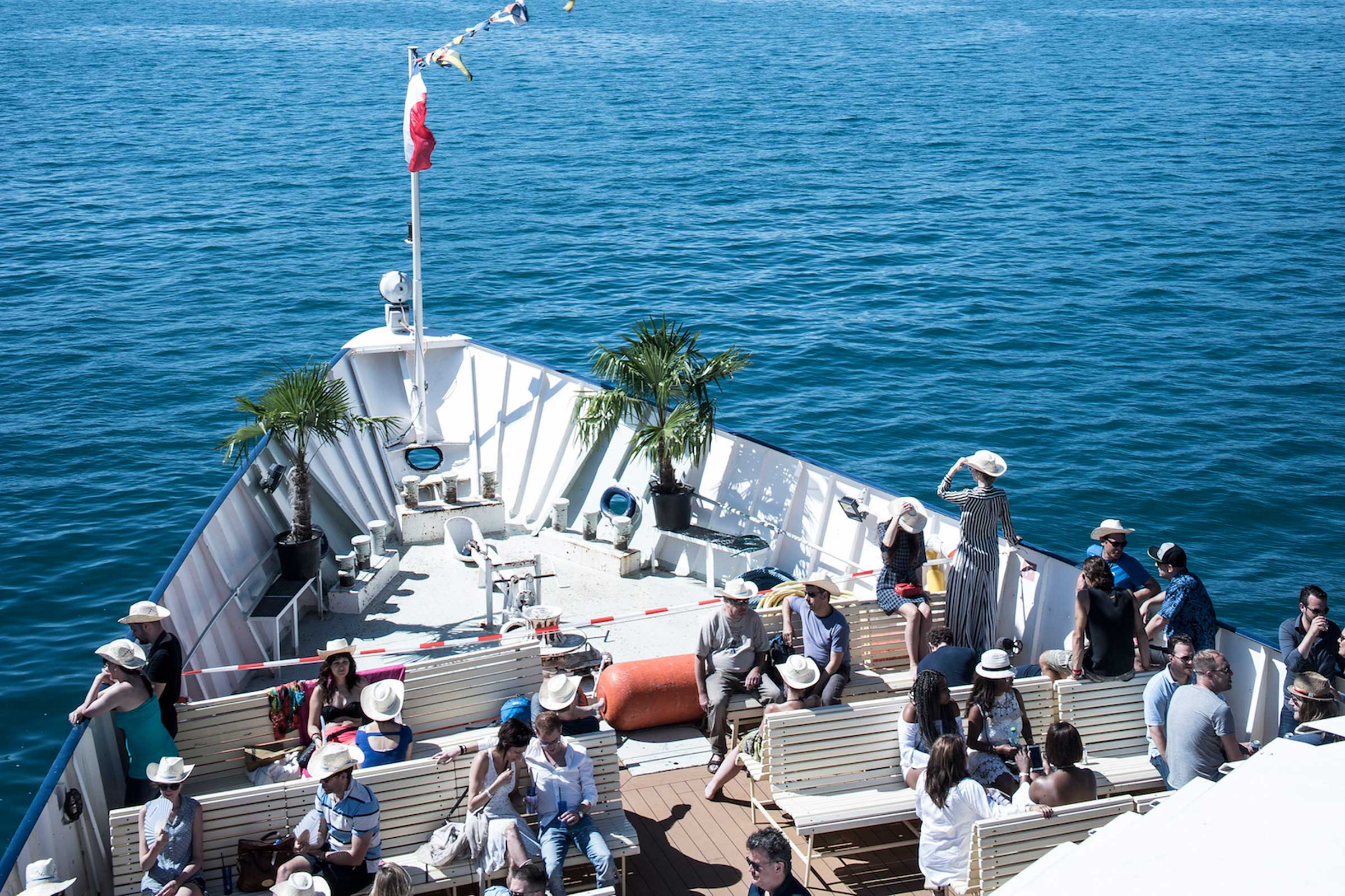 People seated on bench seating in the prow of one of the jazz boats at Montreaux Jazz Festival