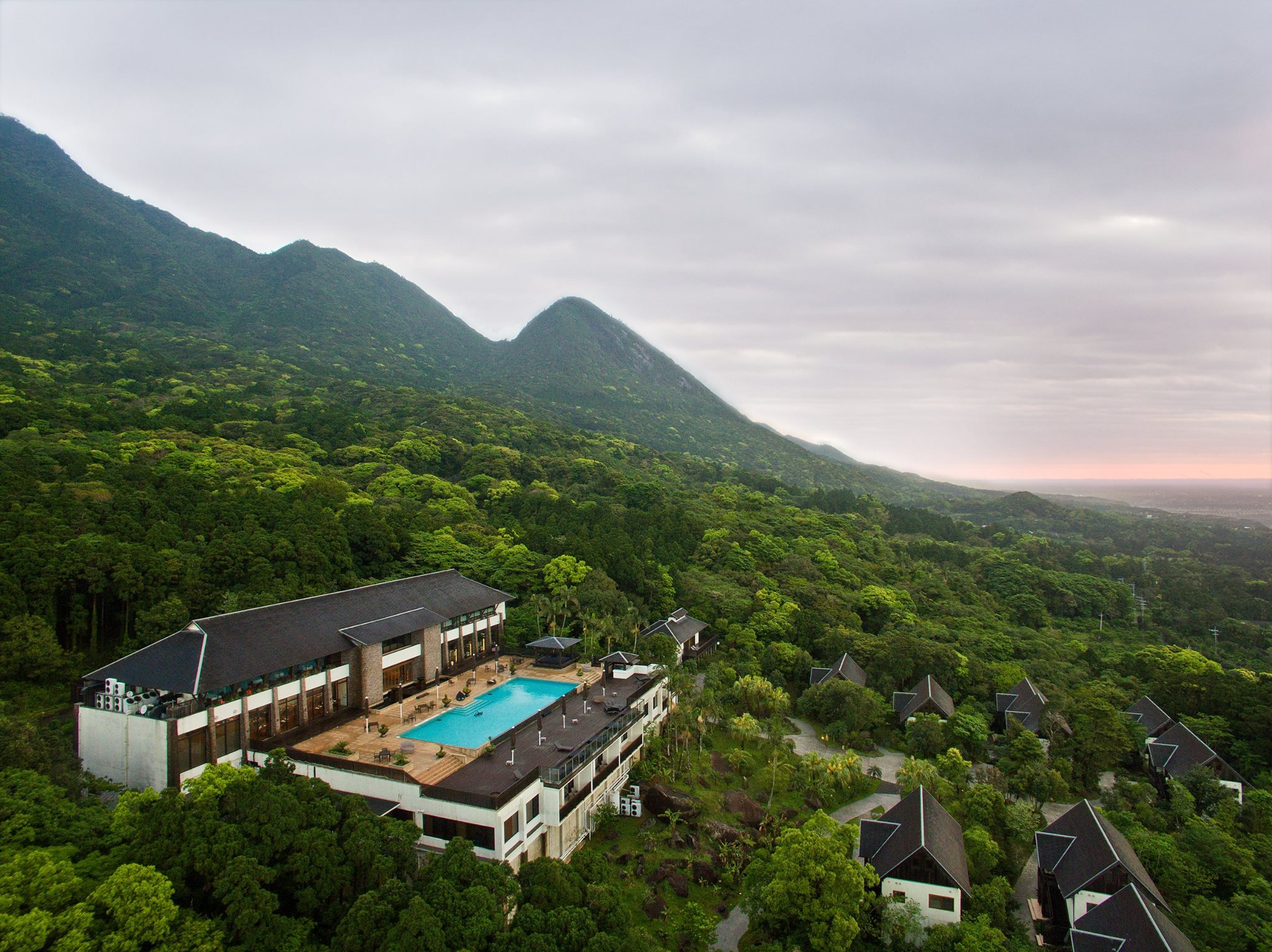 Large hotel with blue swimming pool surrounded by mountains and trees