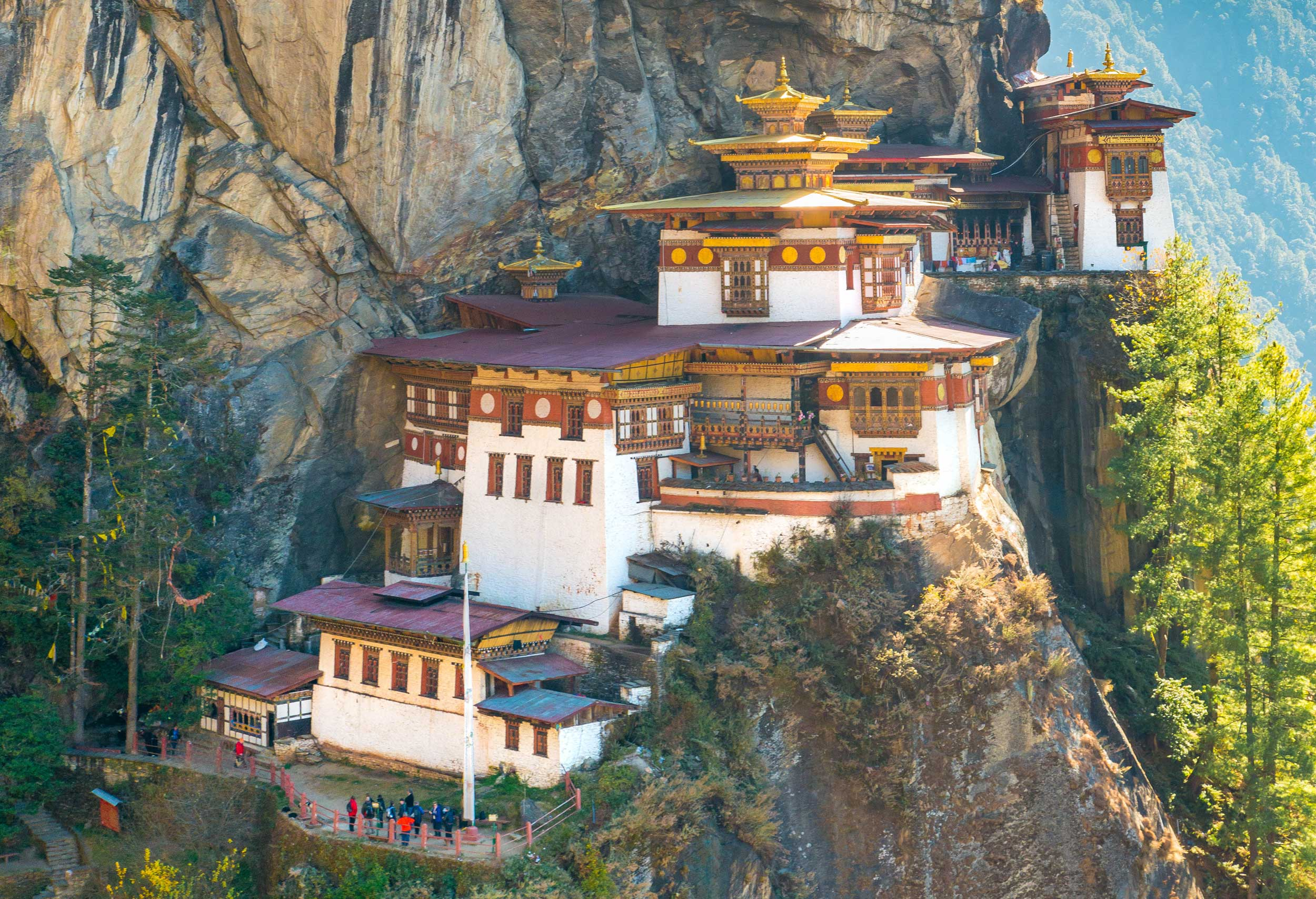 White and red monastery carved into a steep mountain with a sheer drop on one side