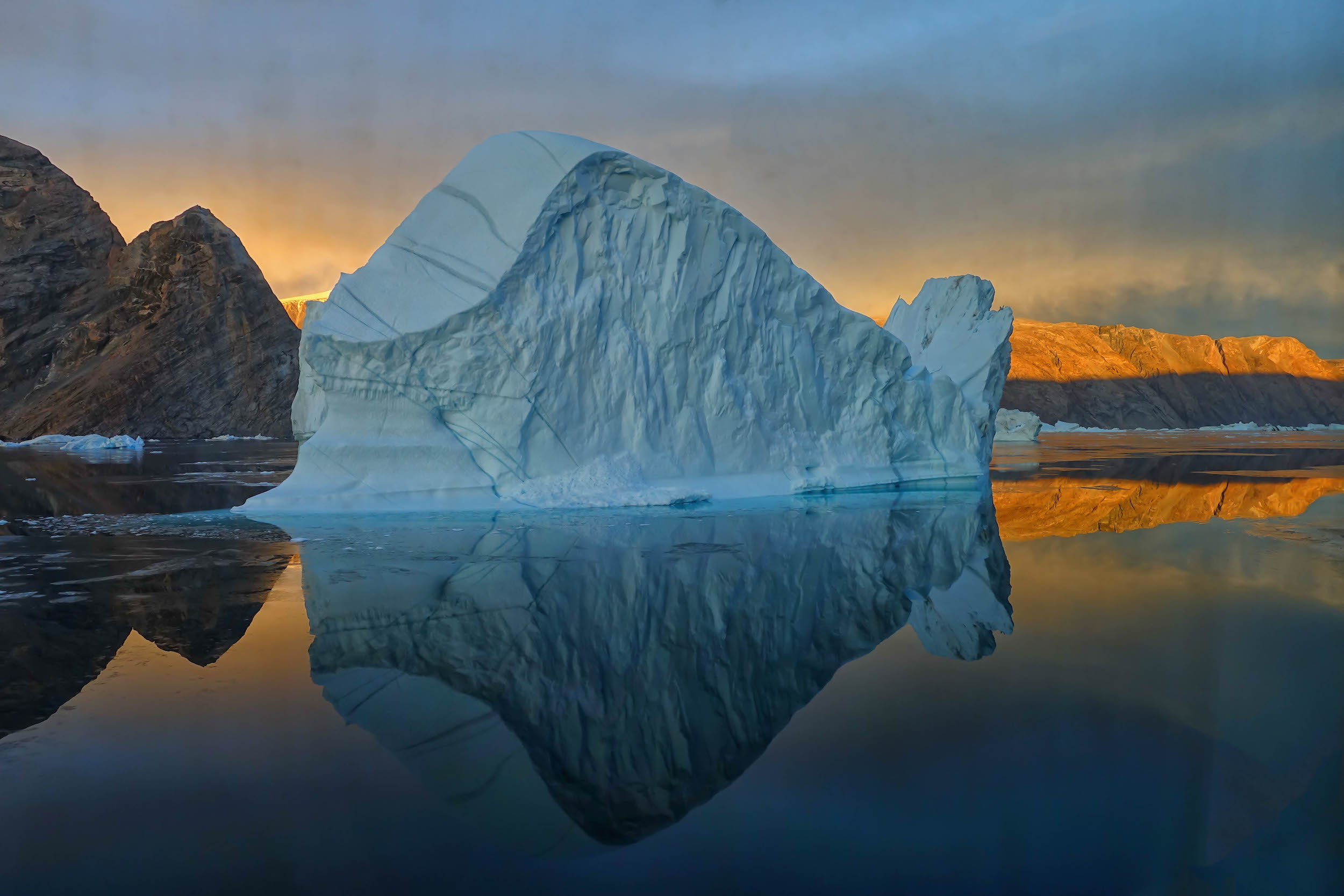 Blue iceberg in front of a setting sun, on a fjord