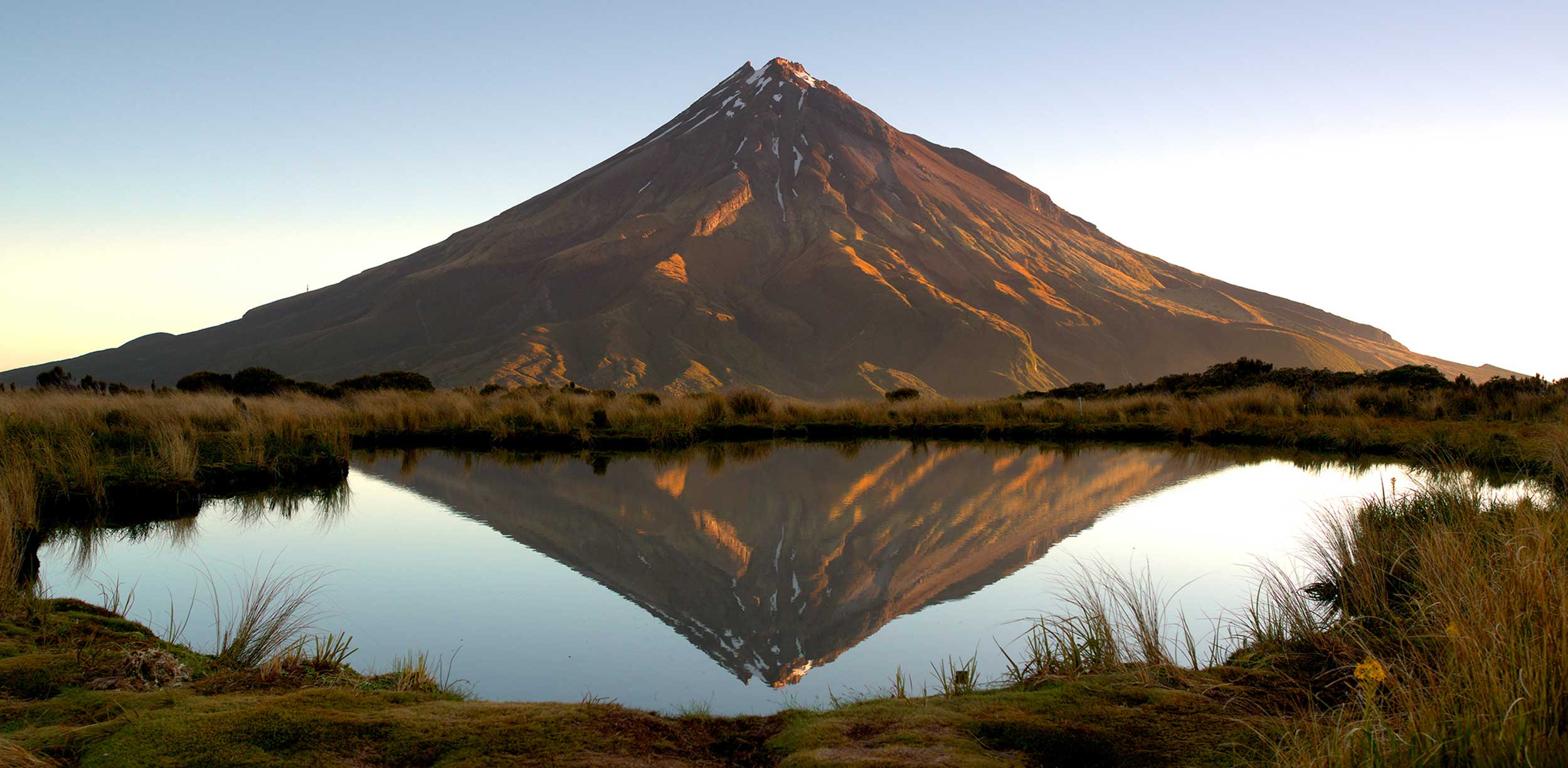 A brown mountain with remnants of snow on its peak reflected in a very still tarn on the Pouakai Crossing, New Zealand