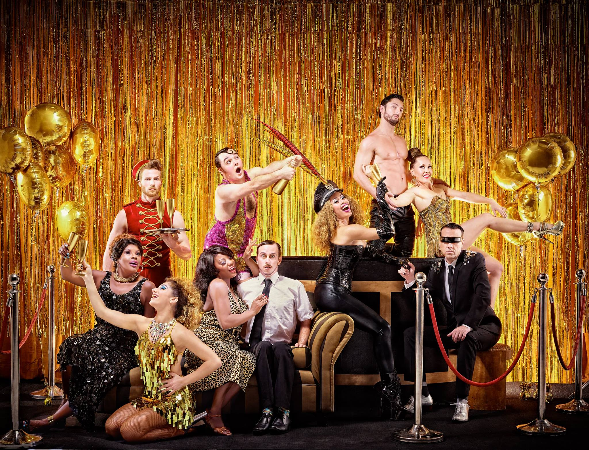 Tableau of people in cabaret costume holding instruments in front of a gold curtain