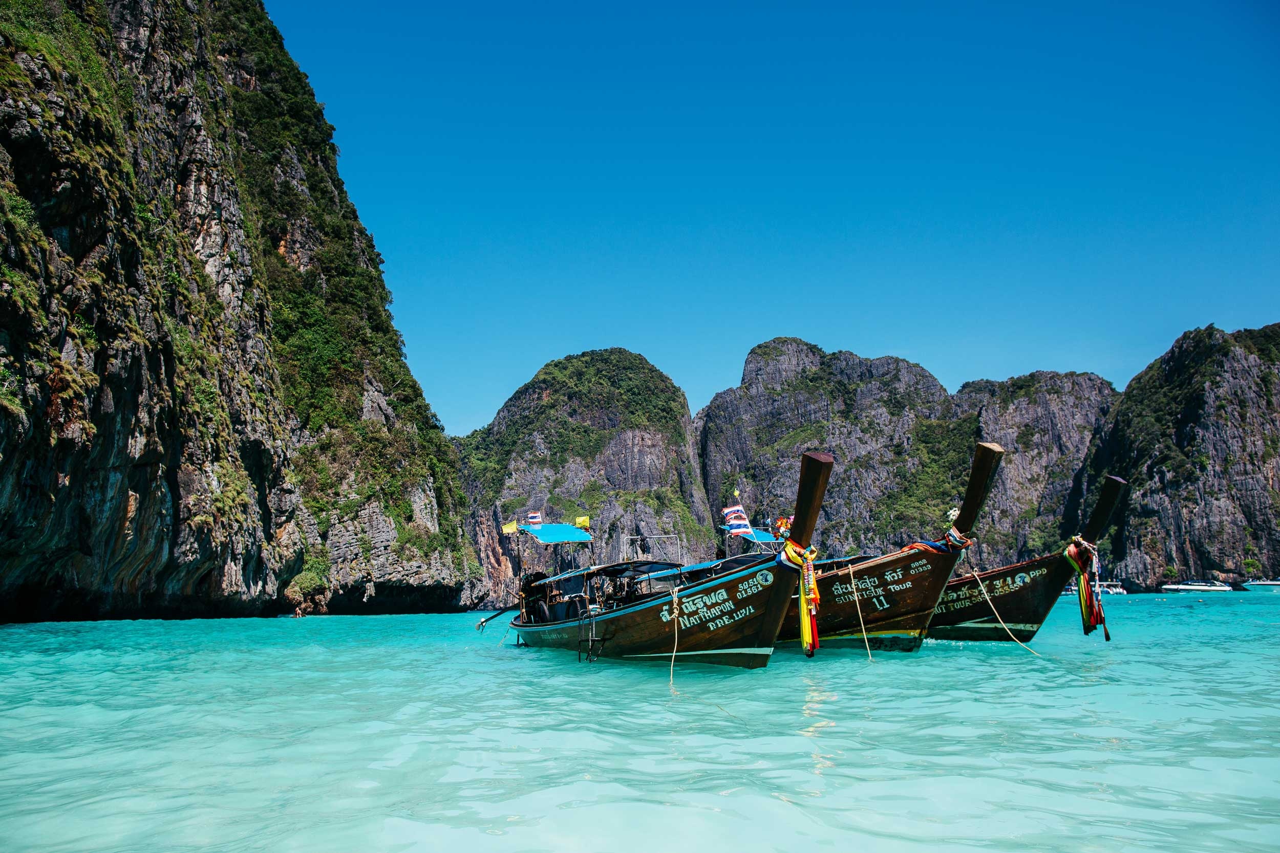 Three moored Thai longtail boats bobbing in clear blue water with rock islands behind them, Maya Bay, Thailand