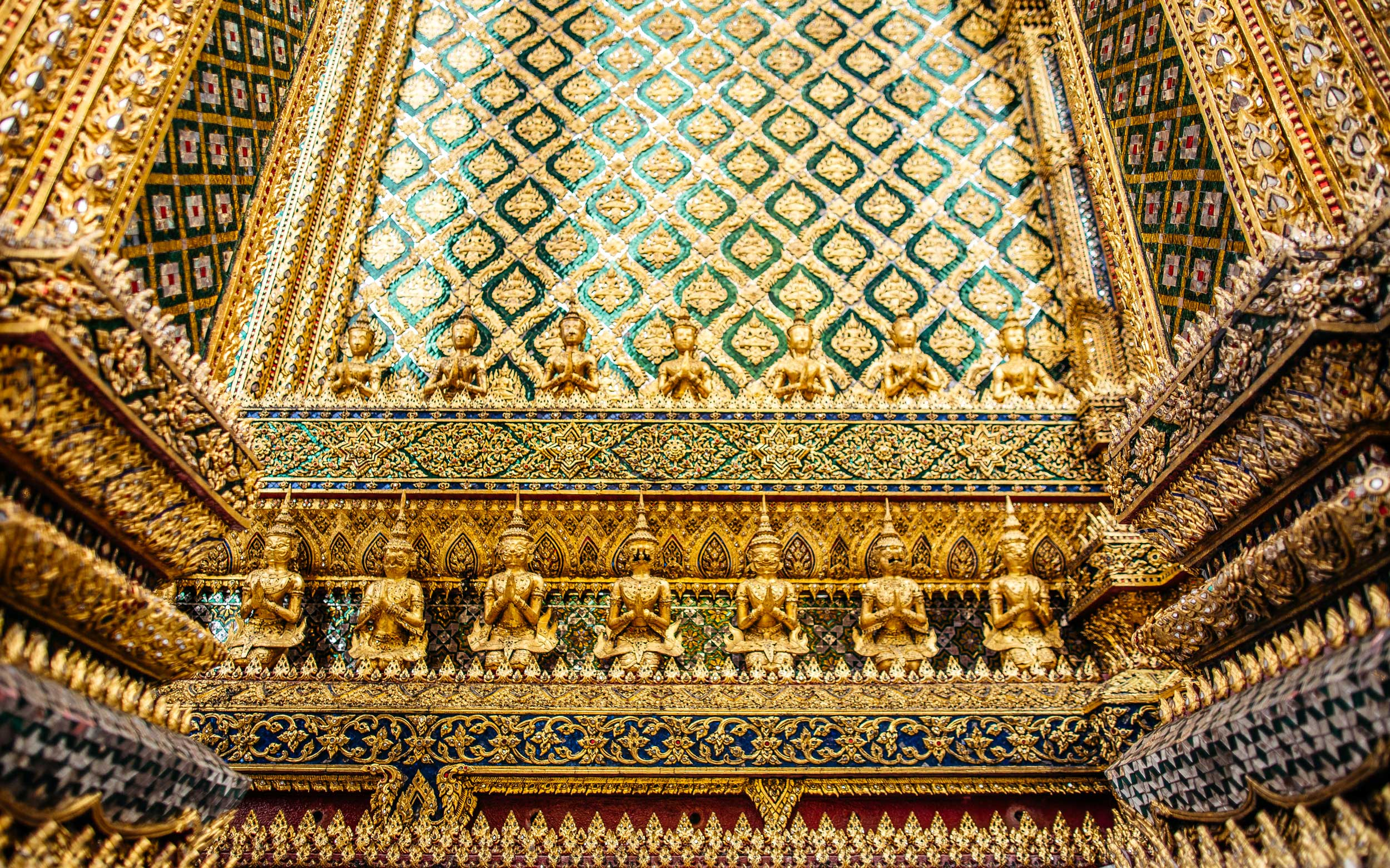 A wall of intricate gold and green filigree design with miniature Buddhas lining it, Thailand