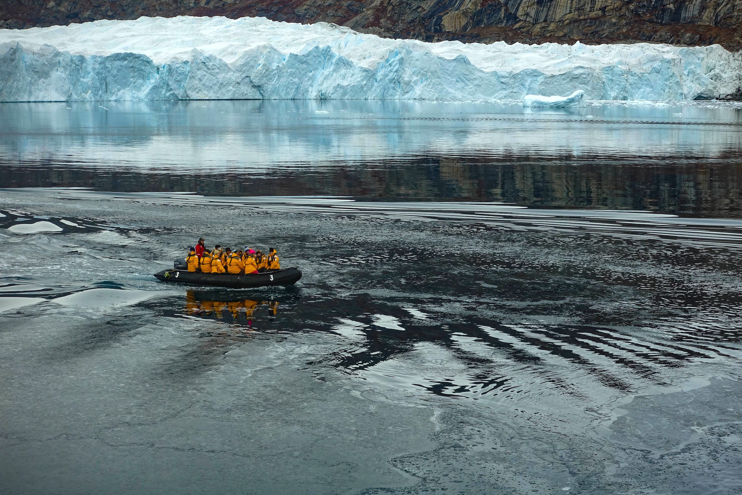 Group in a zodiac boating towards an immense, white iceberg in Greenland