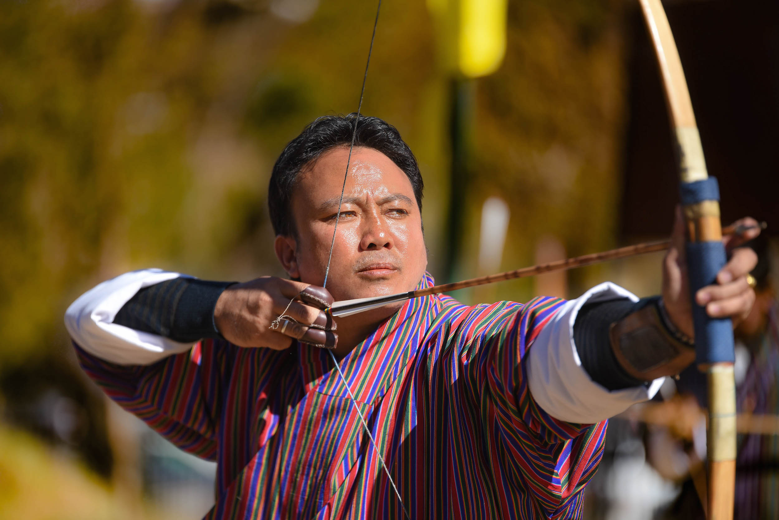 Man in traditional striped Bhutanese dress holding a bow and arrow, ready to fire.