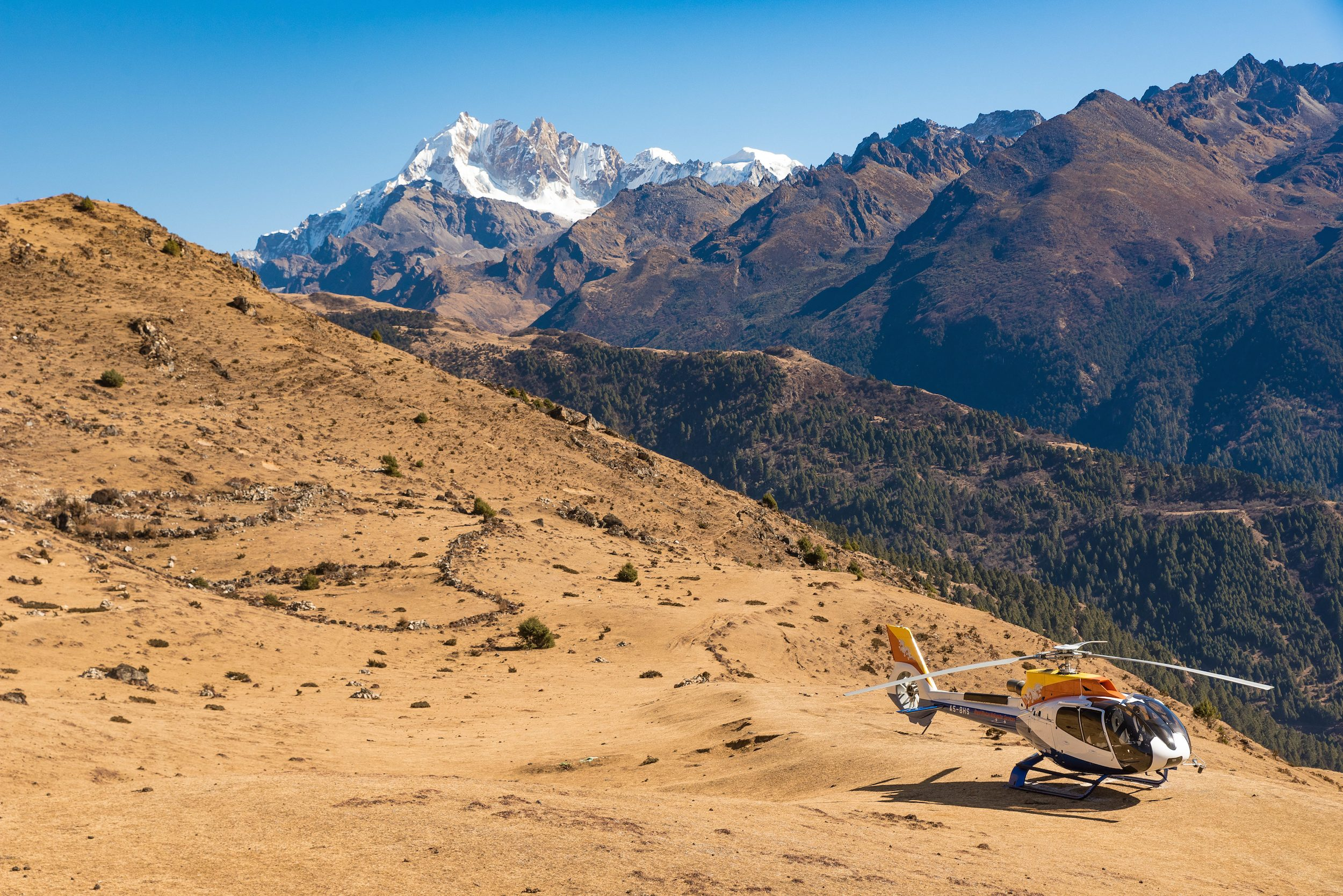 Helicopter on a brown mountainside with icy mountain peaks in the background, Bhutan