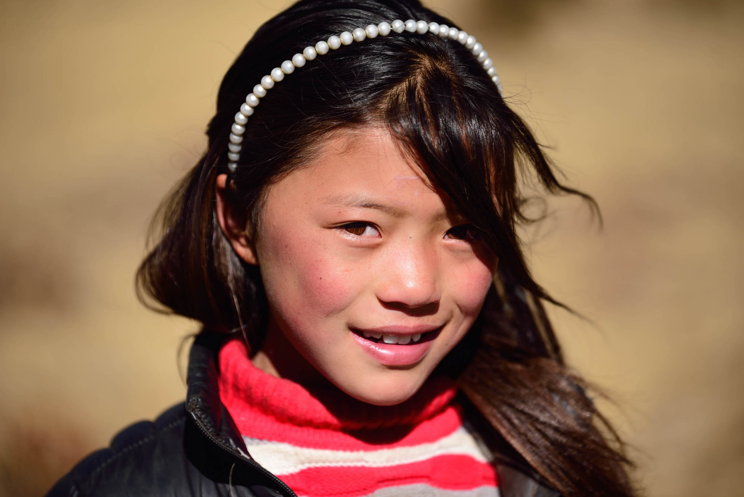 Girl in a stripy top with a faux pearl headband smiles at the camera