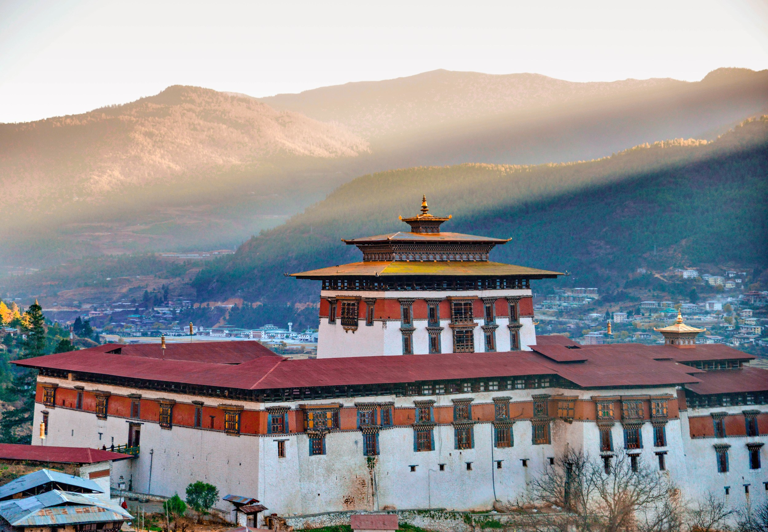 A red and white fortress-like Bhutanese building and a town in the valley beyond it with sunlight streaming between the hills behind it in Bhutan