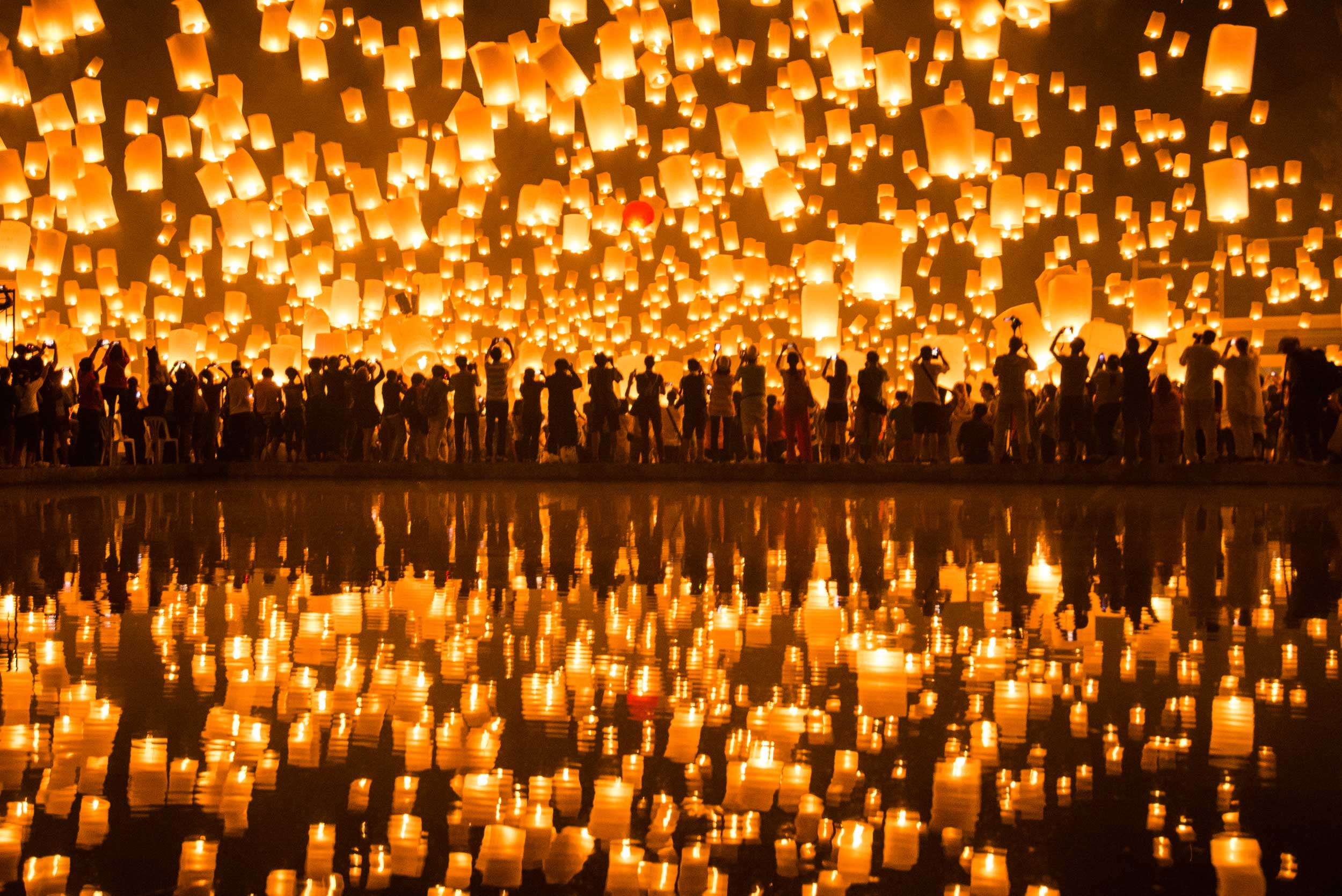A sea of candlelit lanterns rising above a crowd and simultaneously reflected in the water below, Thailand