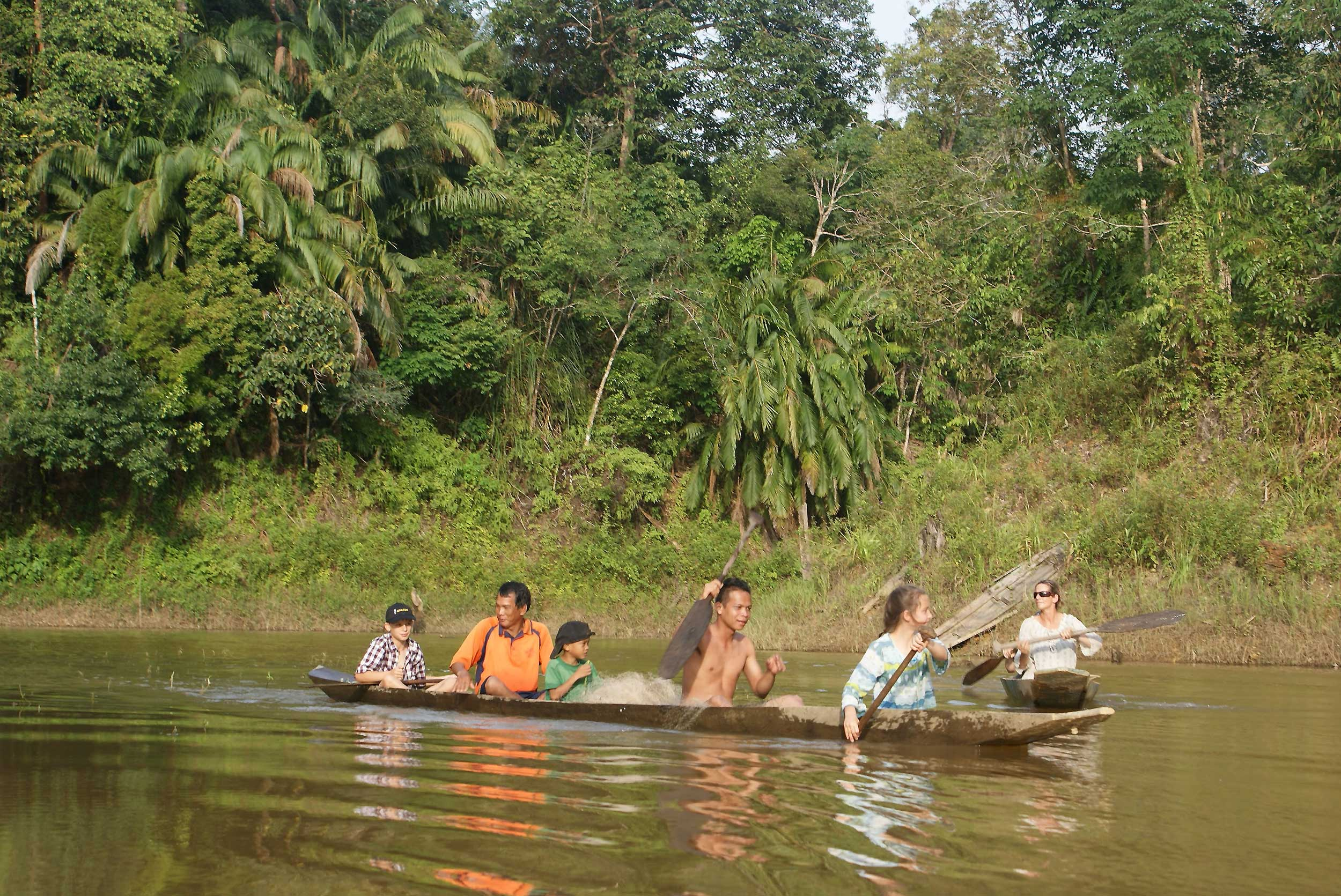 Three children and two adults rowing in a wooden dugout canoe on a river in Borneo
