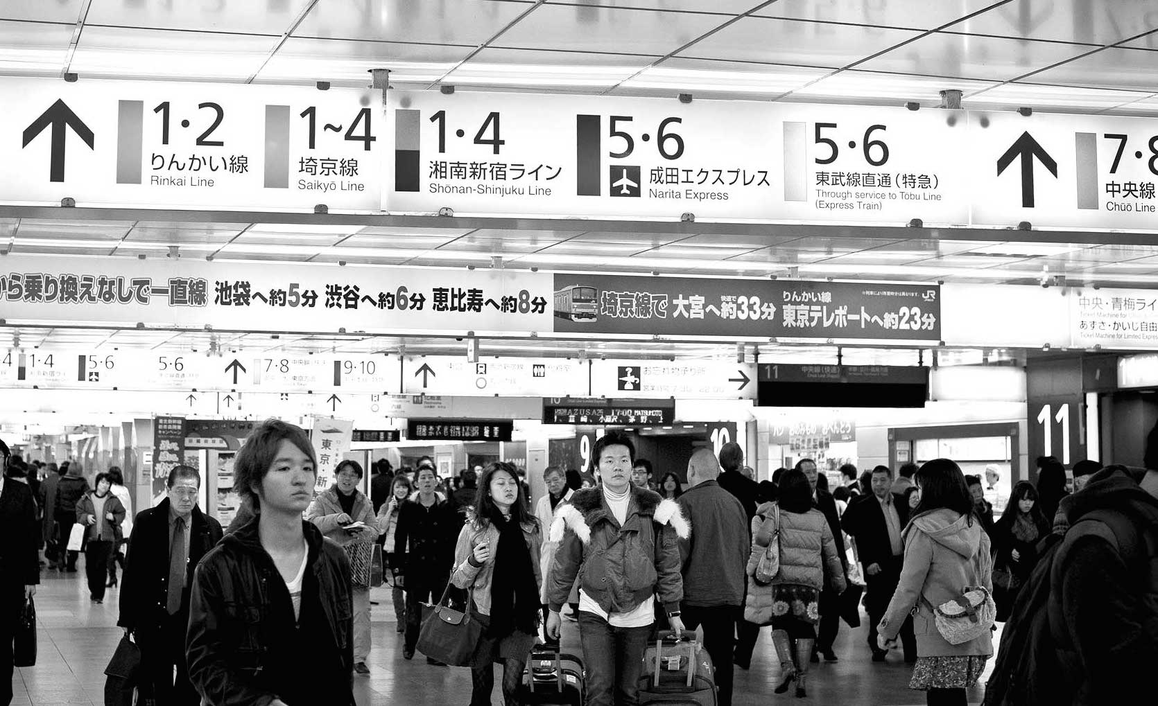 Black and white image of a crowd in Shinjuku station, Tokyo