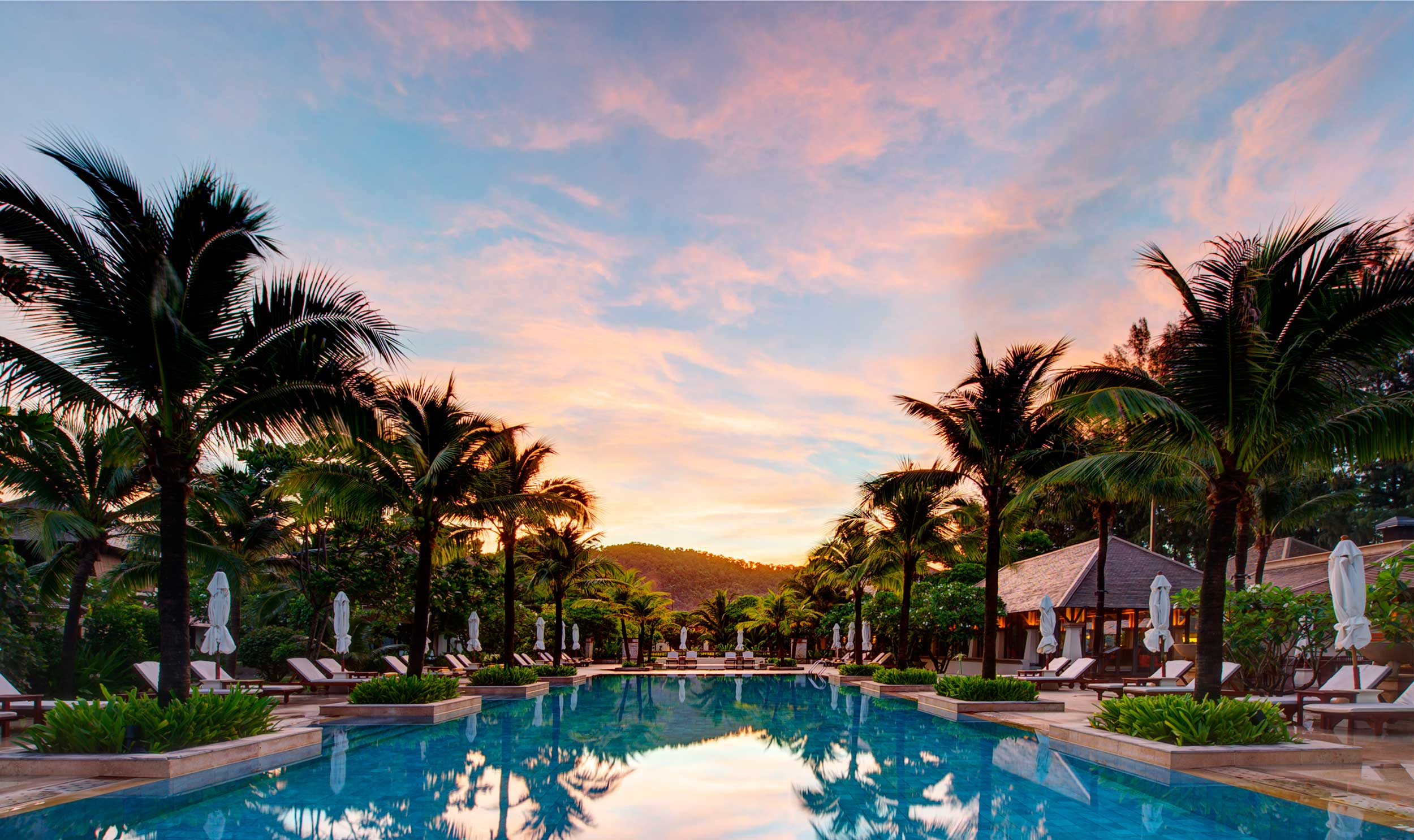 Pink sunset over a swimming pool lined with palm trees