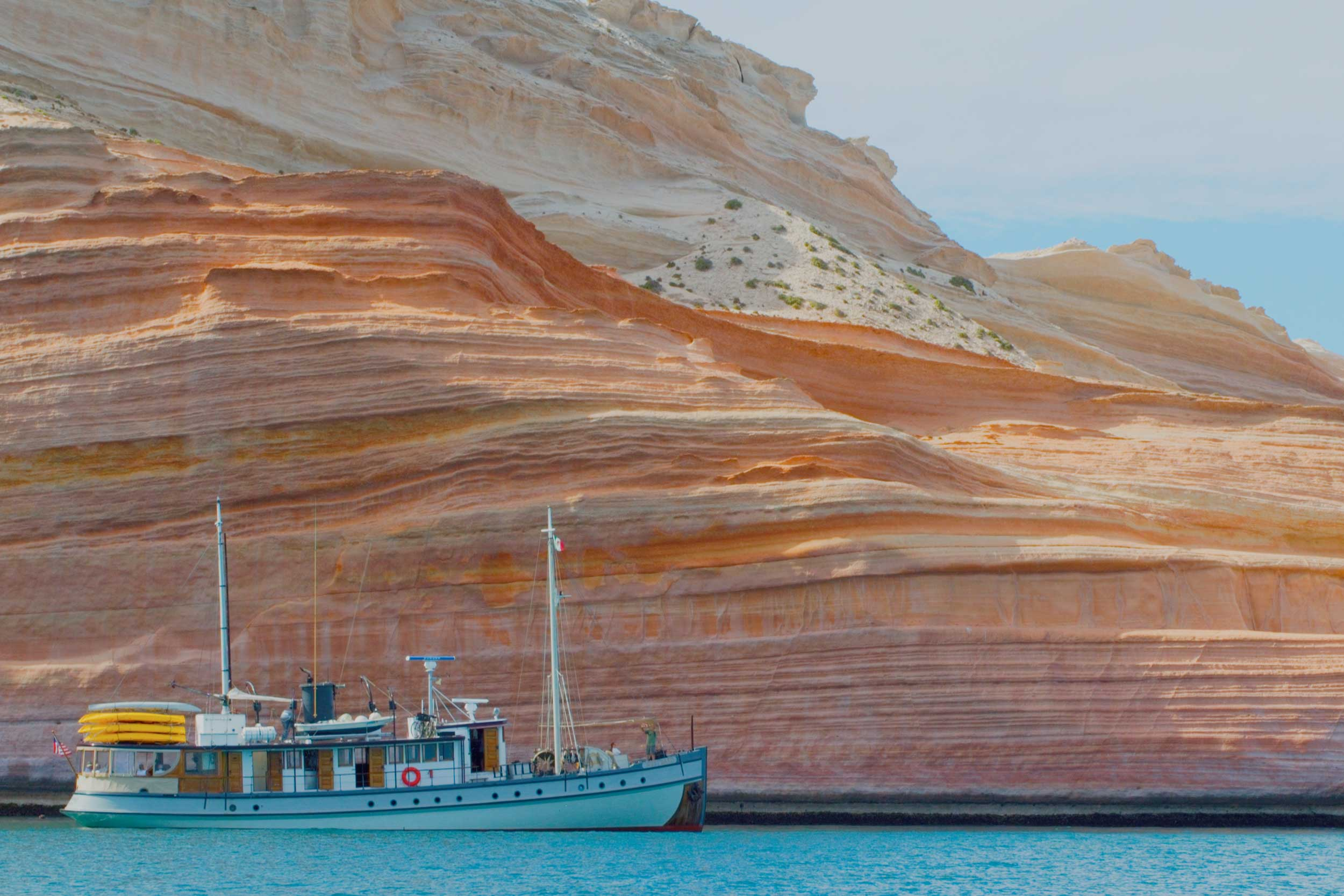 Twin-masted schooner sailing on acquamarine waters past an orange striated rockface, Baja, Mexico