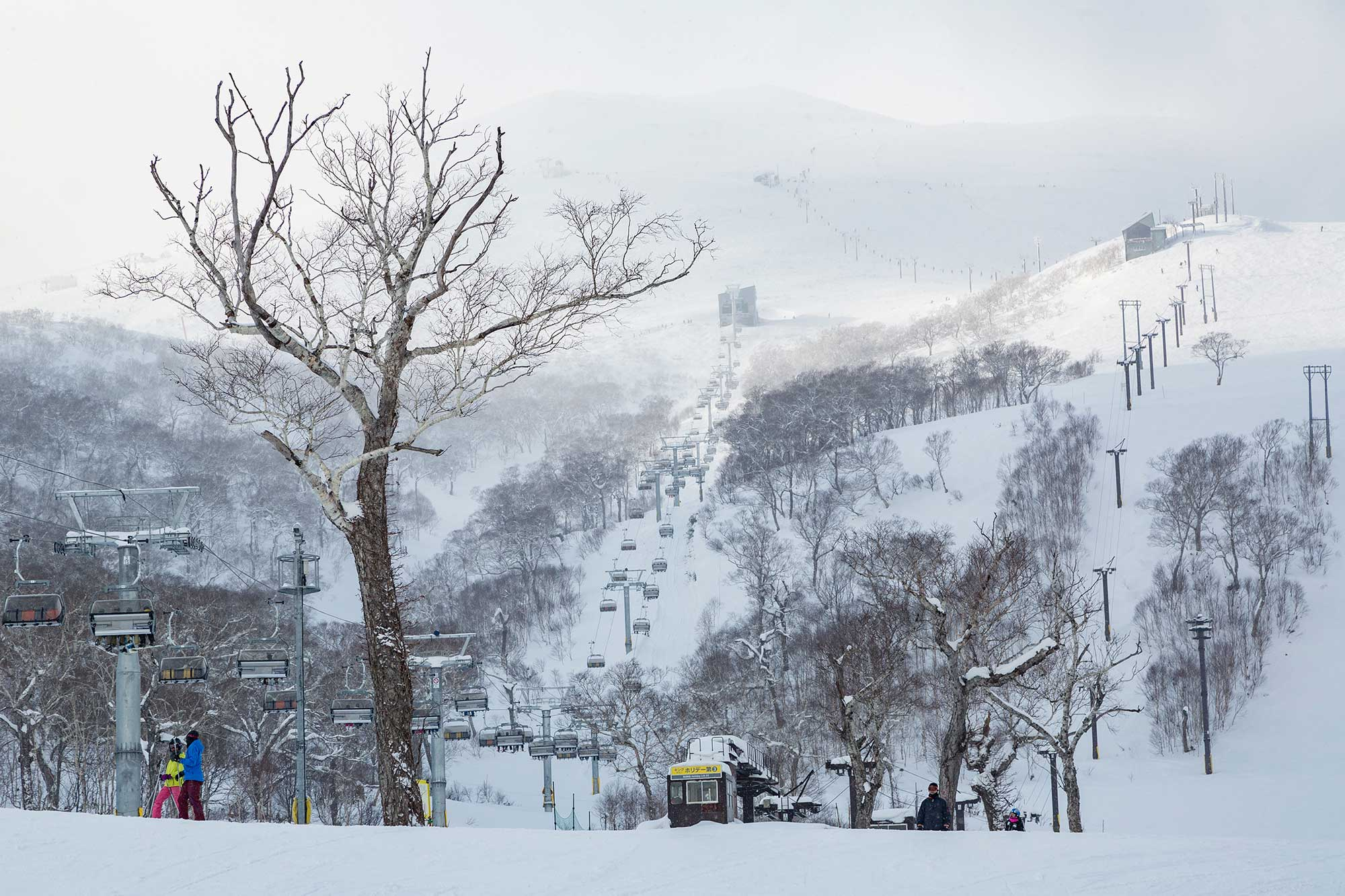 View towards gondolas and chair lifts going up a very snowy mountain