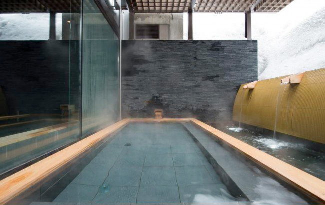A long rectangular outdoor hot spring bath with snow up one side of it in Niseko, Japan