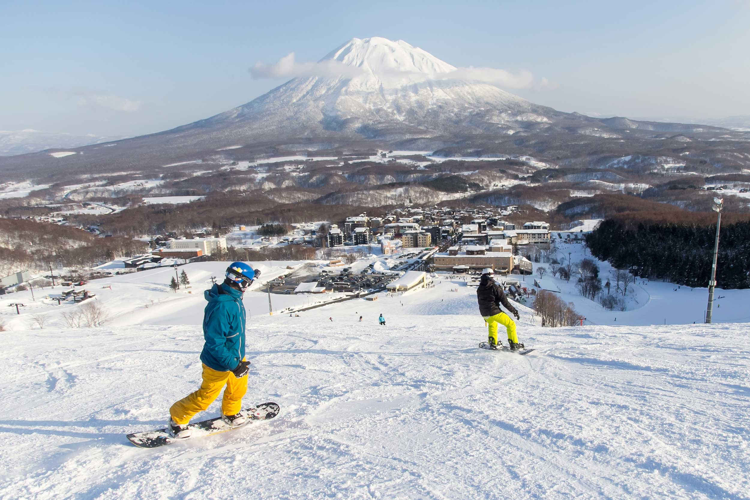 Snowboarders on a snowy slope, a ski resortat the bottom and a conical, snow-capped mountain in the distance, Japan